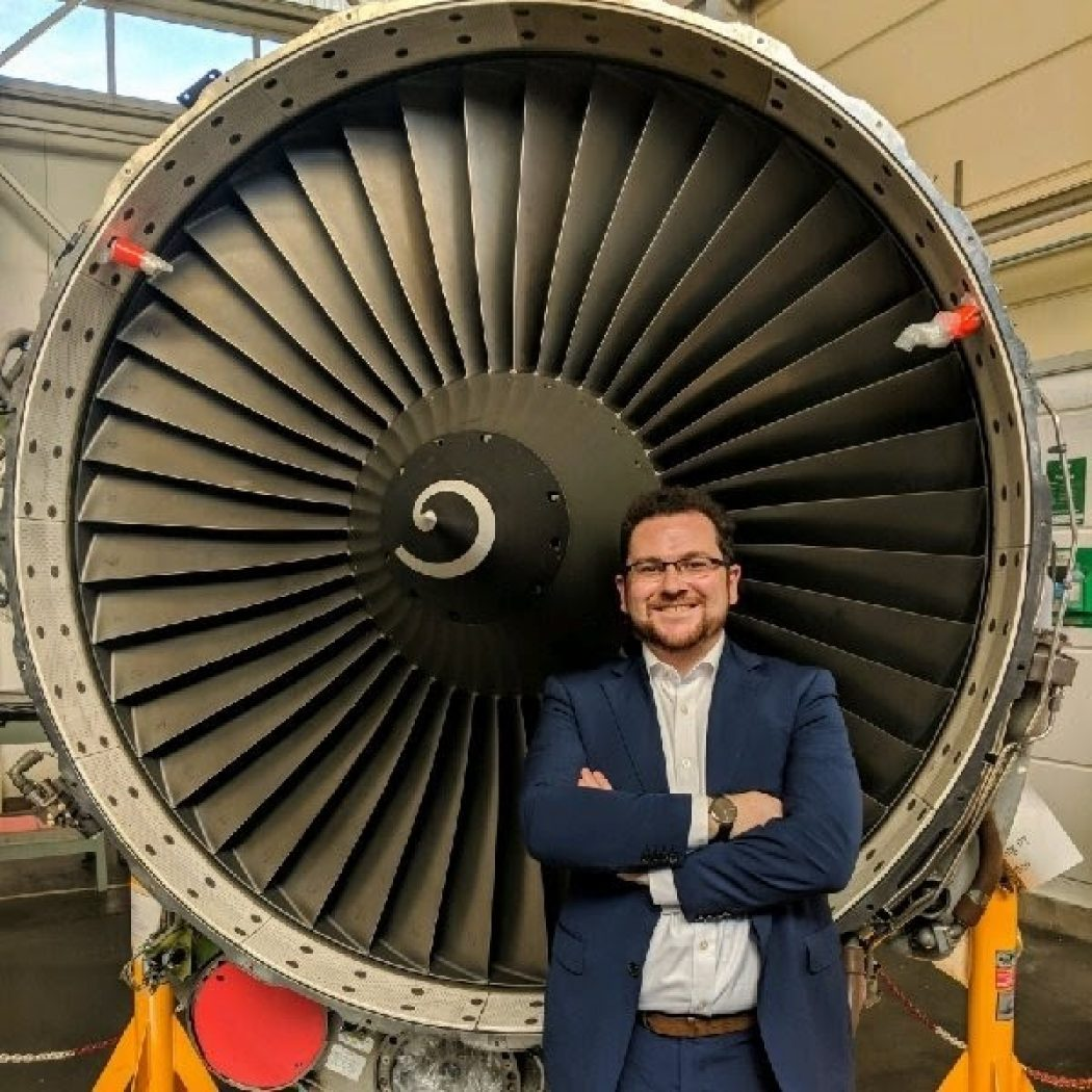 Colin Geraghty standing in front of a jet engine