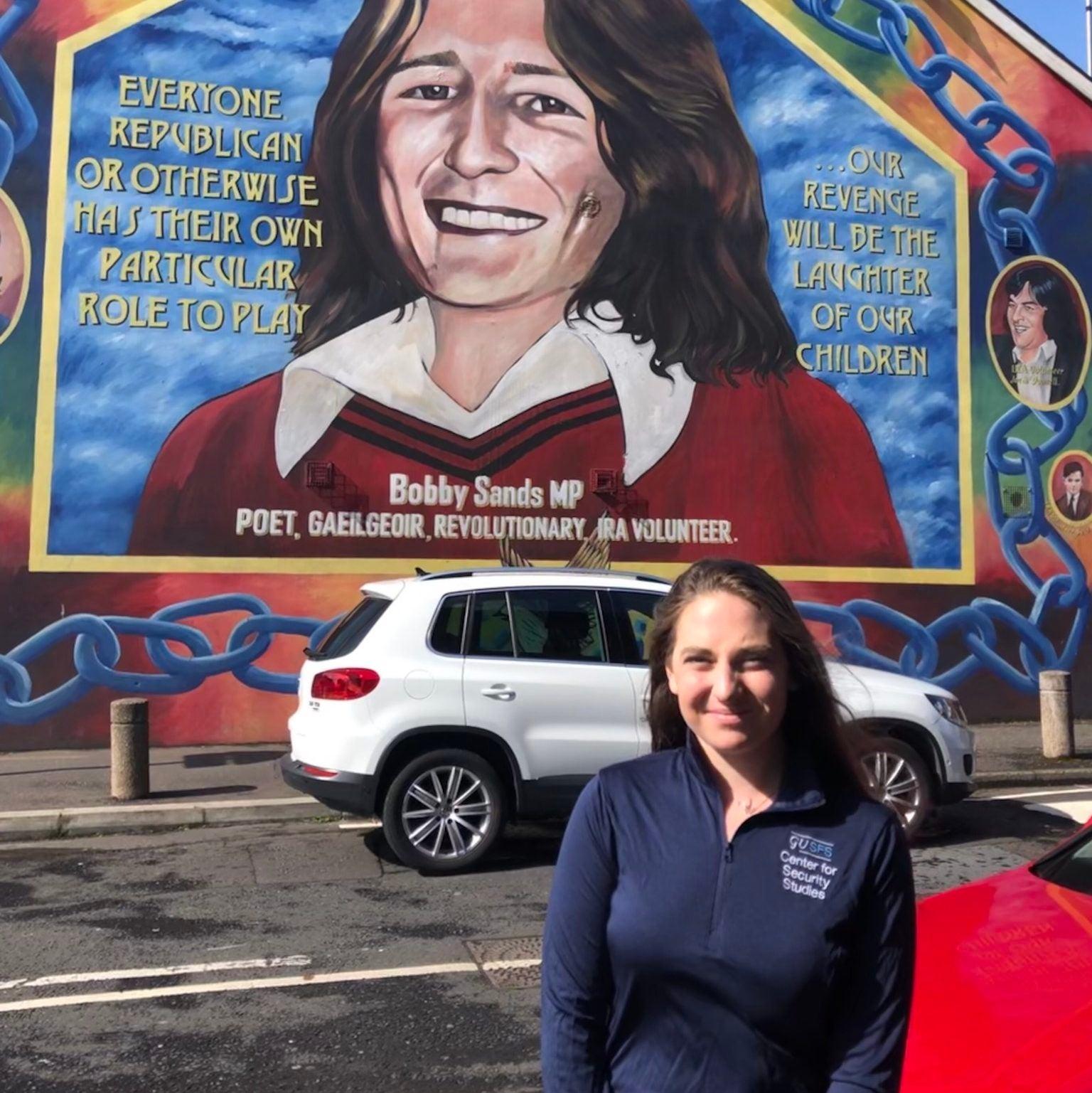 Rebecca Malone in front of a mural in Belfast