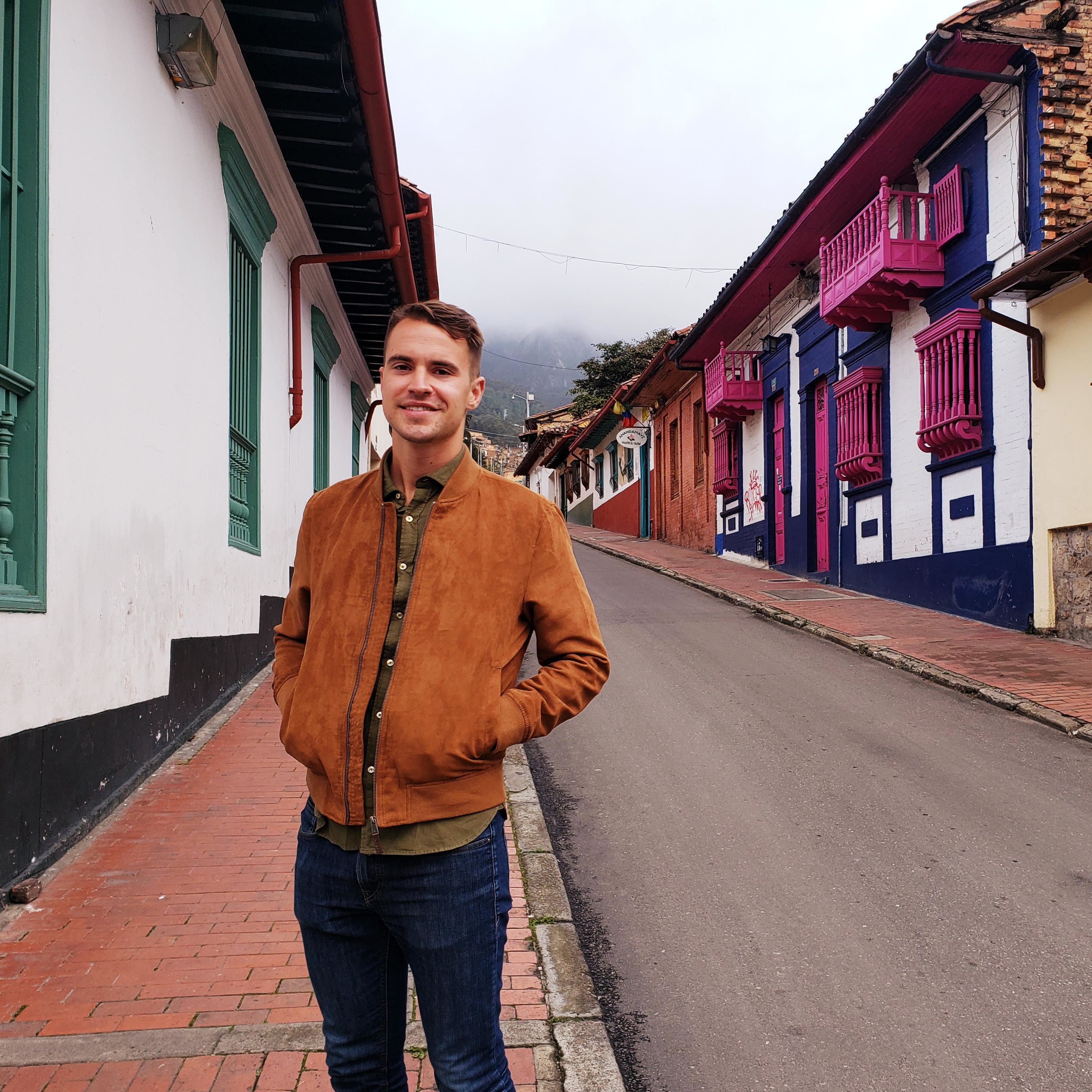 Sam Riddell in front of a row of houses in Colombia