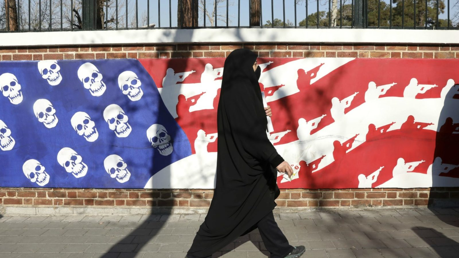 A mourner passes in front of an anti-American flag design on the wall of the former U.S. Embassy in Tehran.