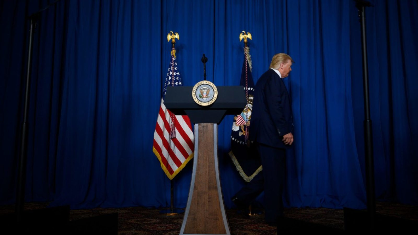 Donal Trump leaves the podium on a darkened stage.