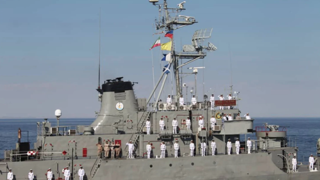 Warship with sailors in white uniforms.