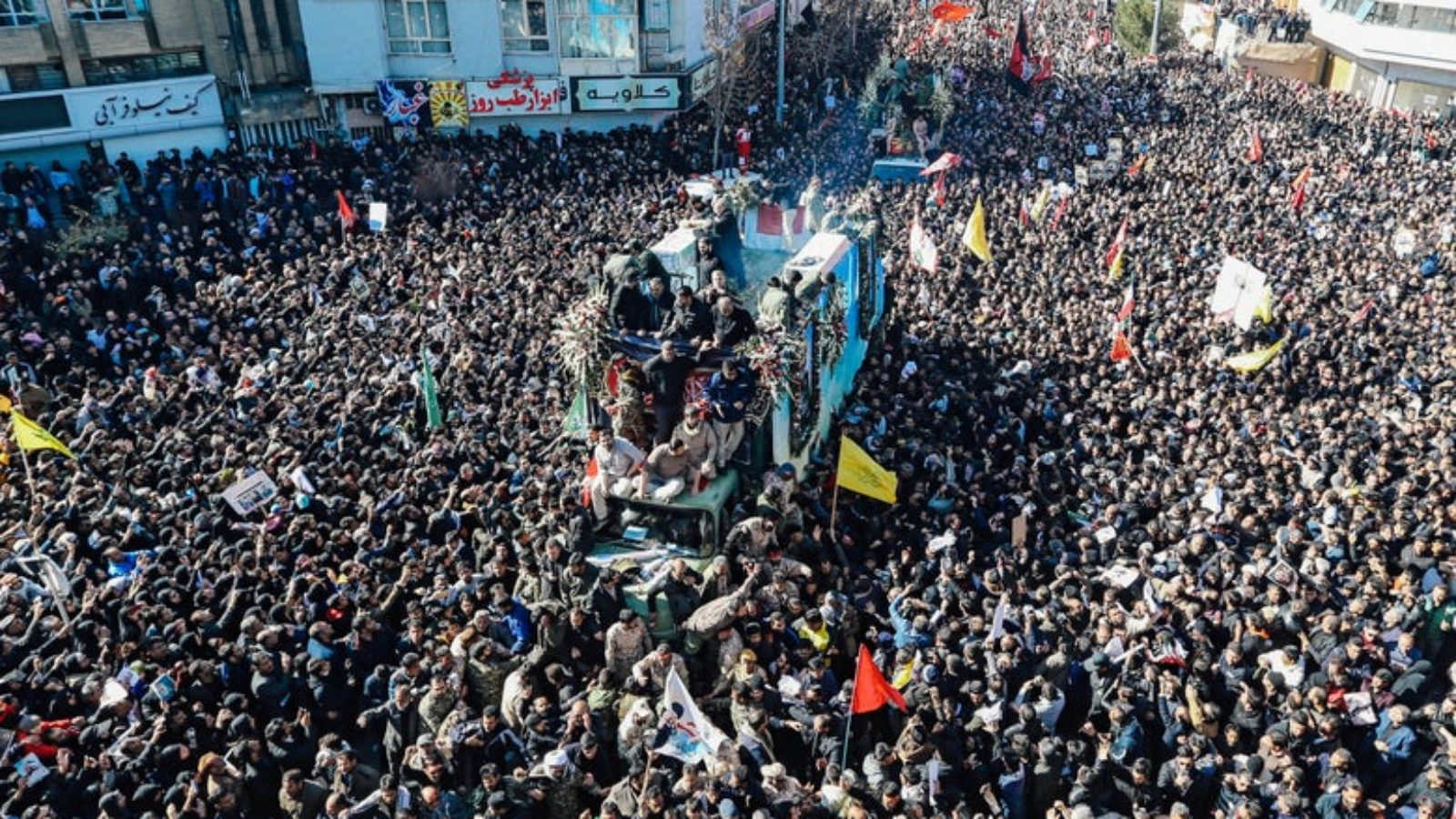 Thousands of Iranian mourners gather around a vehicle carrying the coffin of Qassem Soleimani.