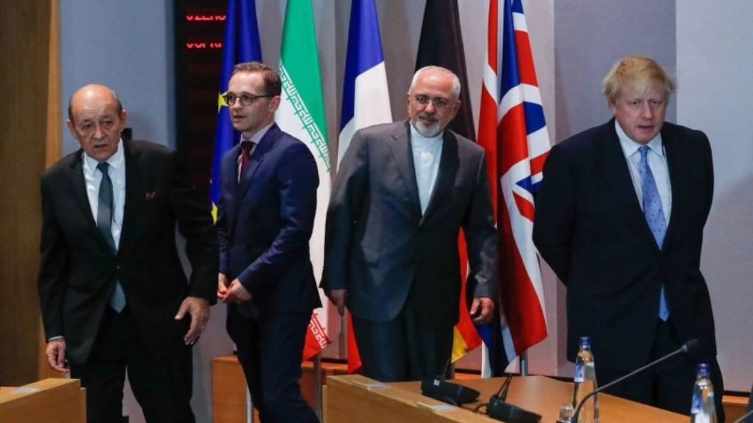 Jean-Yves Le Drian, Heiko Maas, Javad Zarif, and Boris Johnson stand in front of flags.