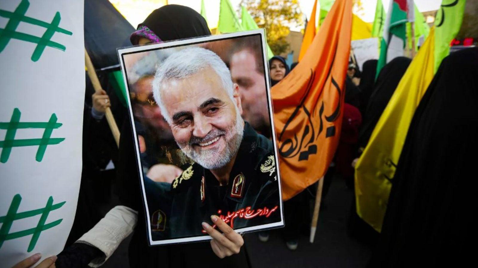 Iranian protesters hold a photo of Maj. Gen. Qassem Suleimani
