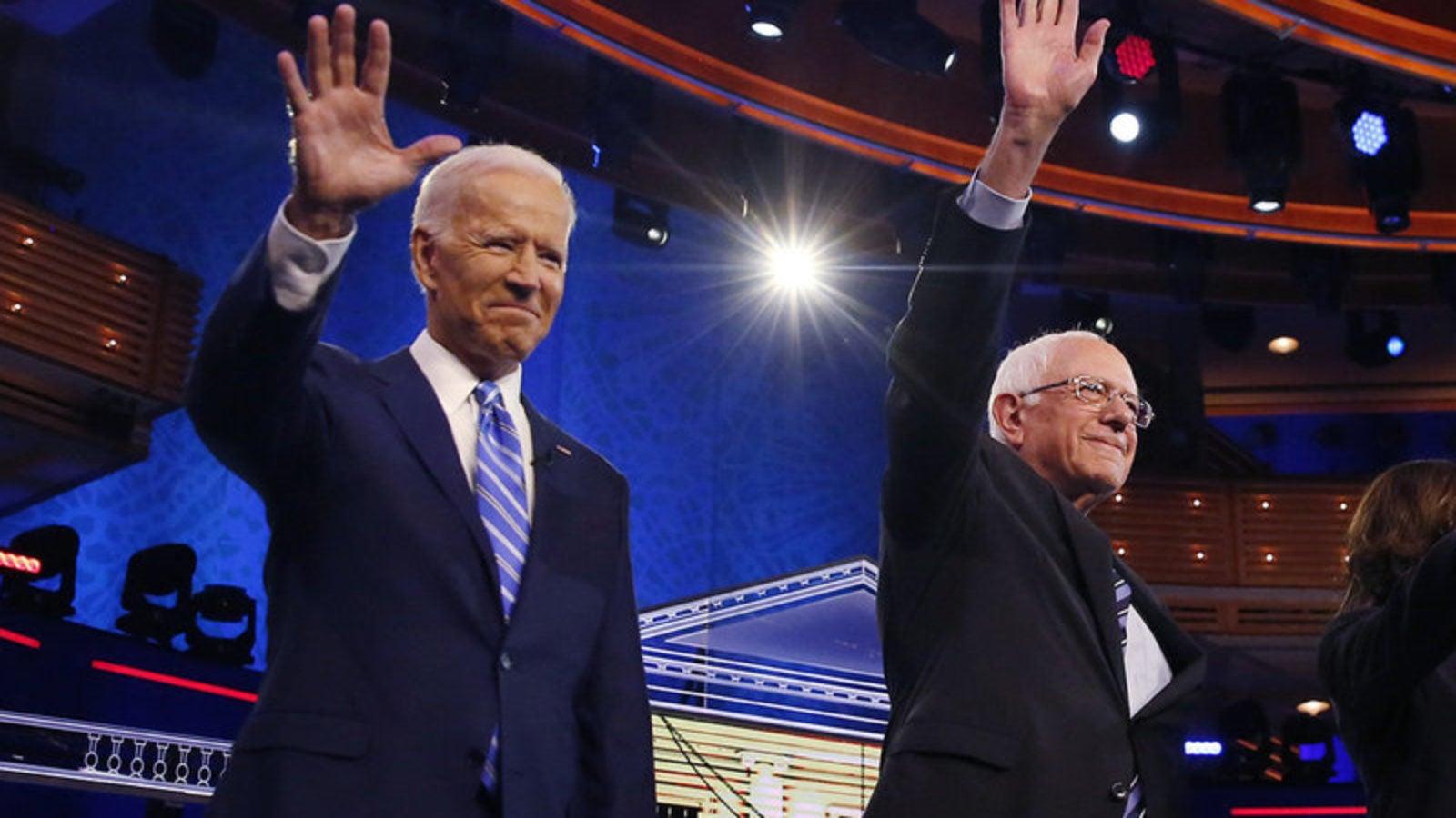 Joe Biden and Bernie Sanders on a debate stage wave at the audience.