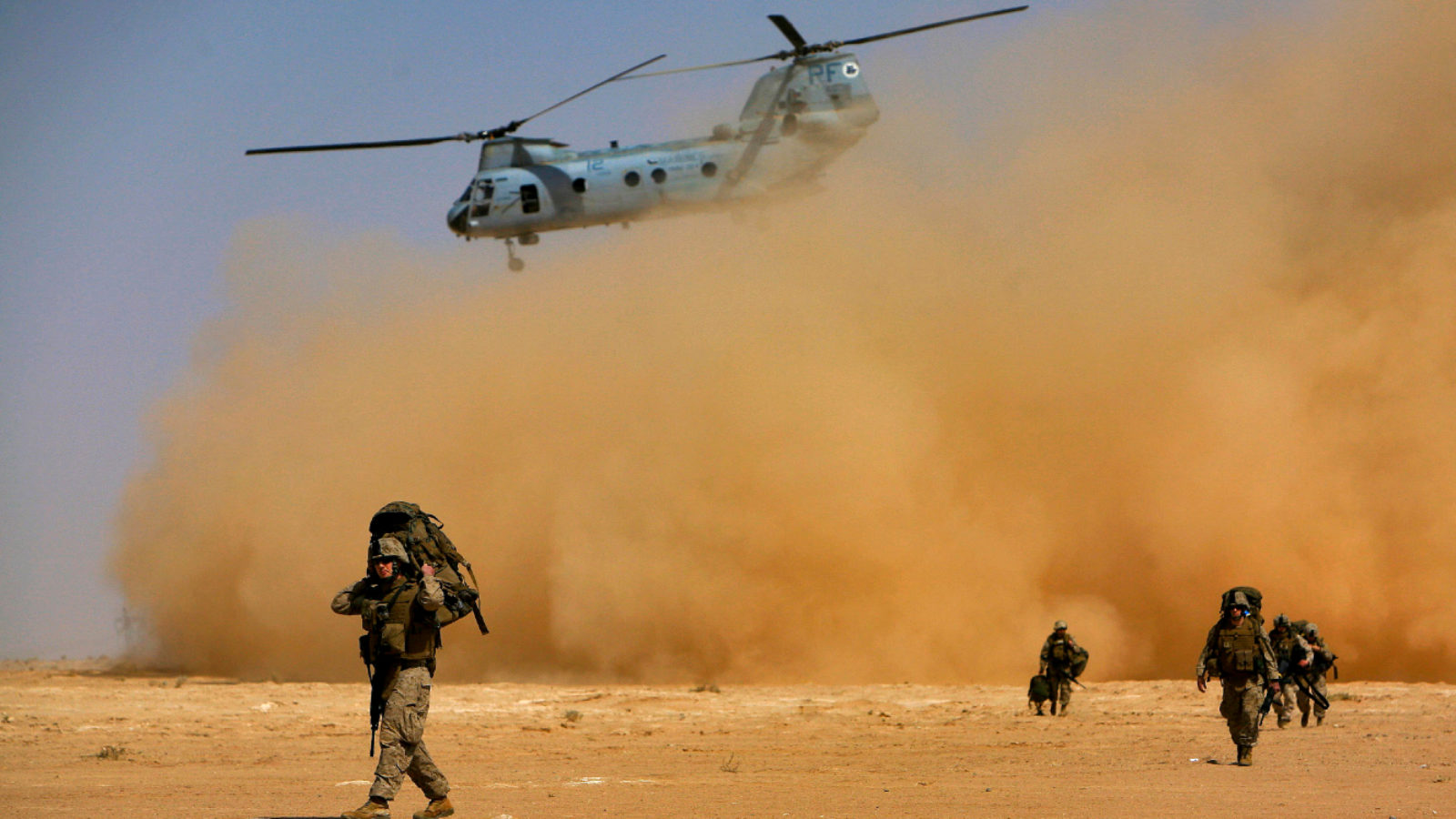 Soldiers walk in a desert underneath a departing Chinook helicopter.