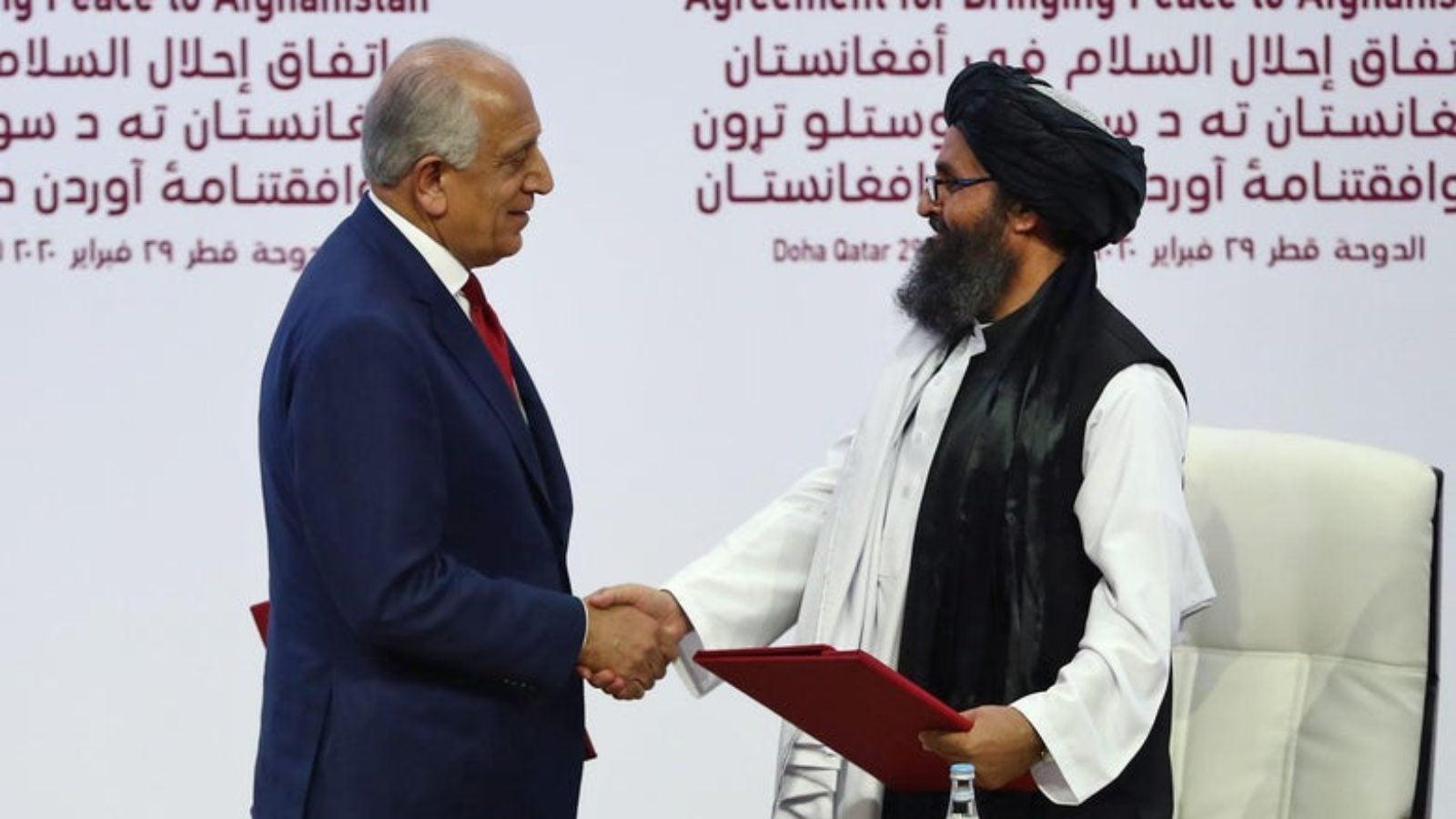U.S. peace envoy Zalmay Khalilzad, left, and Mullah Abdul Ghani Baradar, the Taliban's top political leader, shake hands after signing a peace agreement between Taliban and U.S. officials in Doha, Qatar.