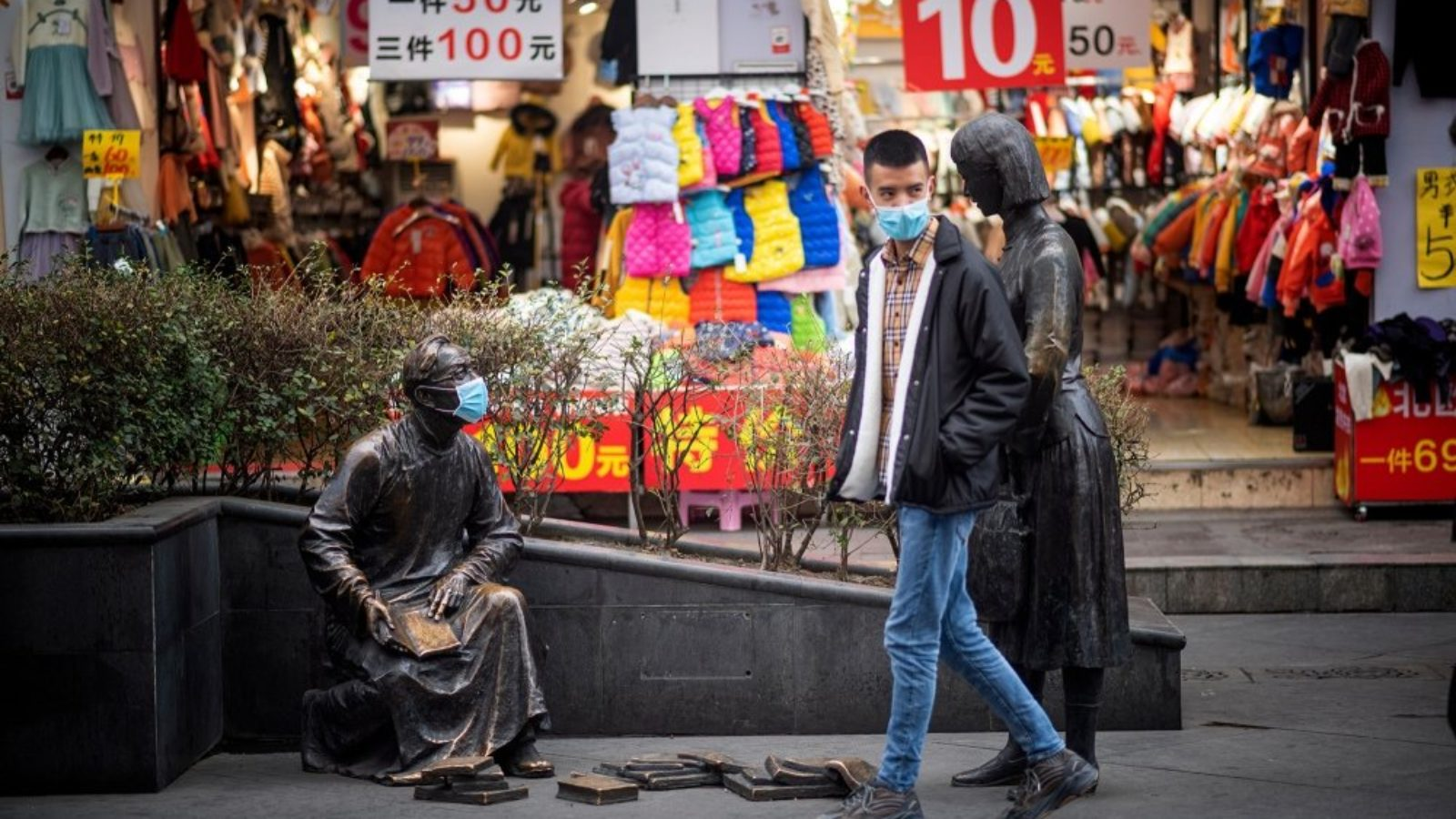 A person wearing a surgical mask walks by a storefront and a statue also wearing a mask.