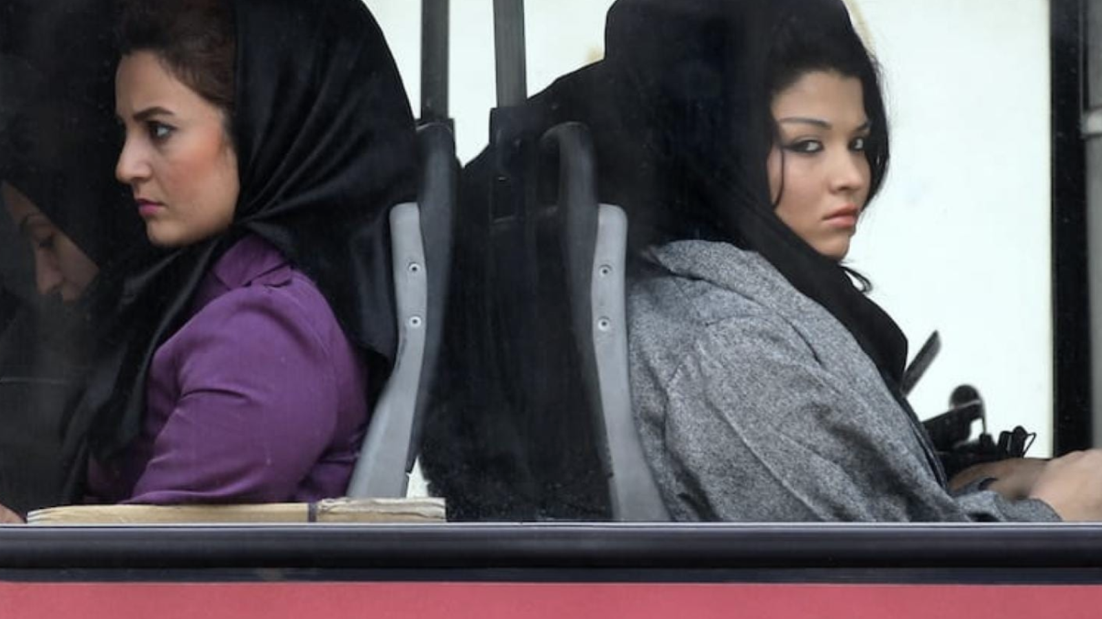 Iranian women look out from a bus