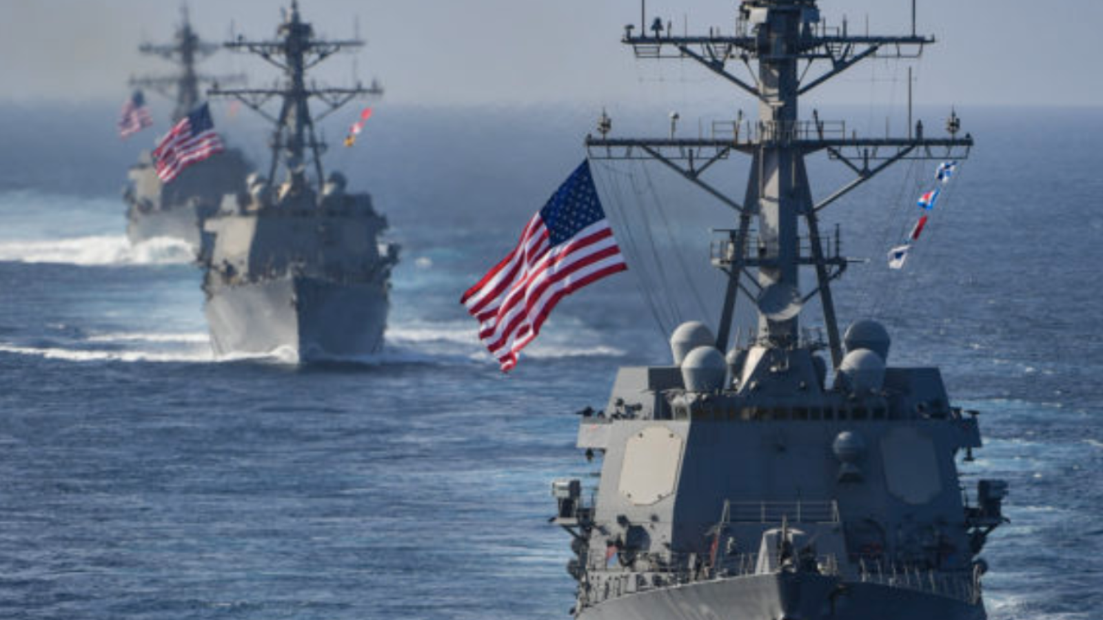 Three Navy destroyers flying American flags at sea