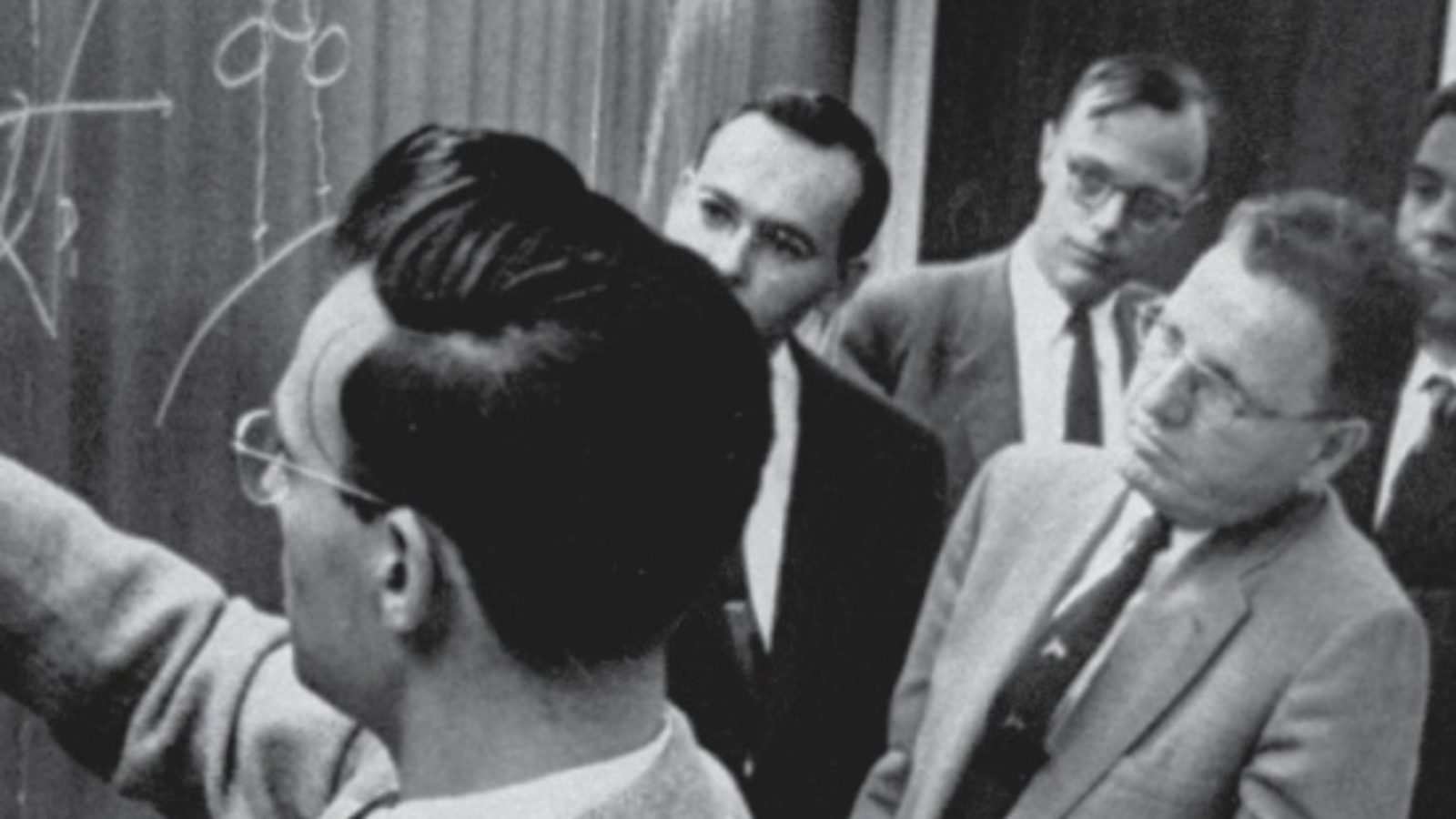 A monochrome photo of men in suits looking at graphs on a blackboard.