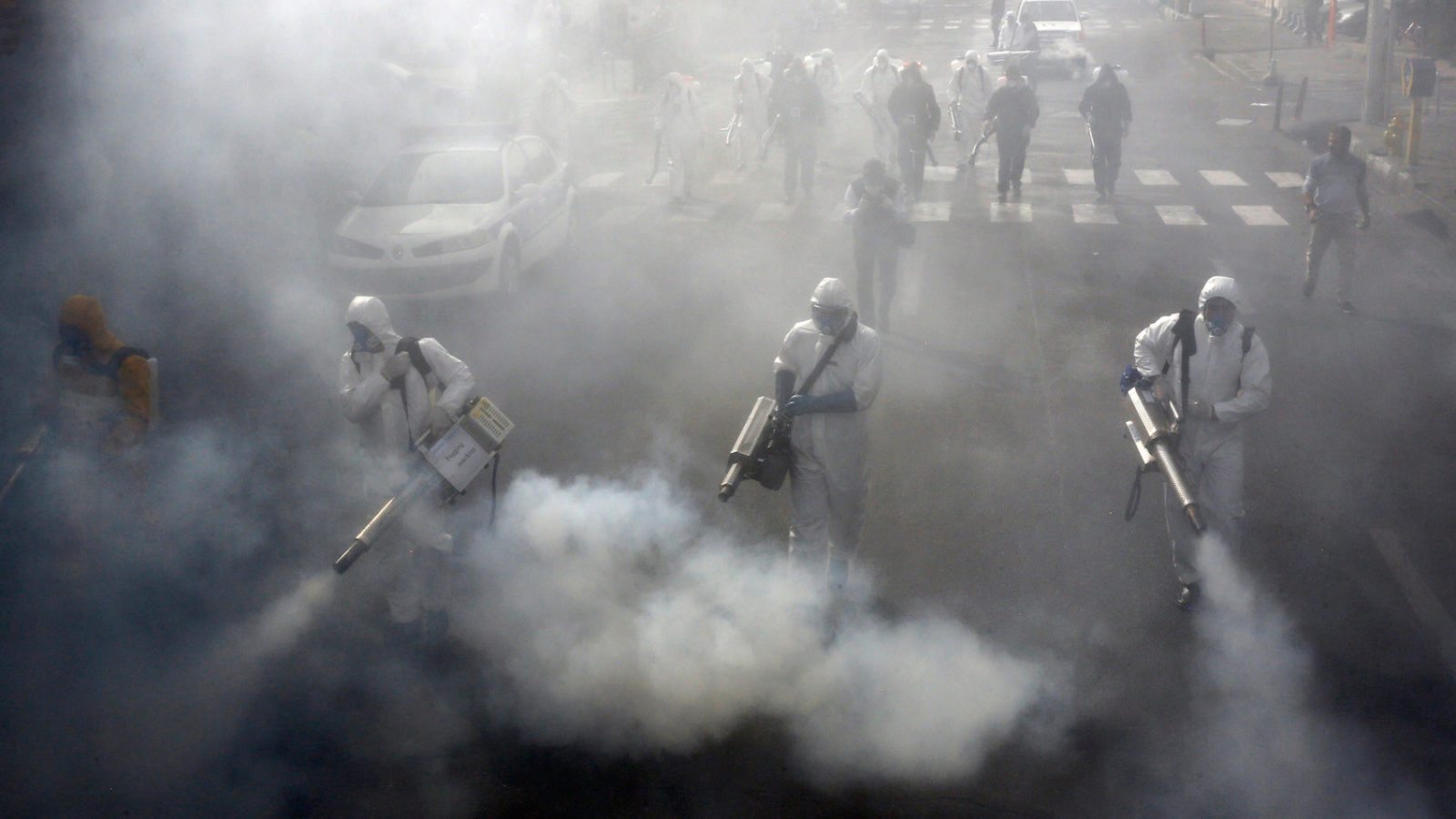 Iranian firefighters disinfect streets in Tehran in a bid to halt the spread of the coronavirus
