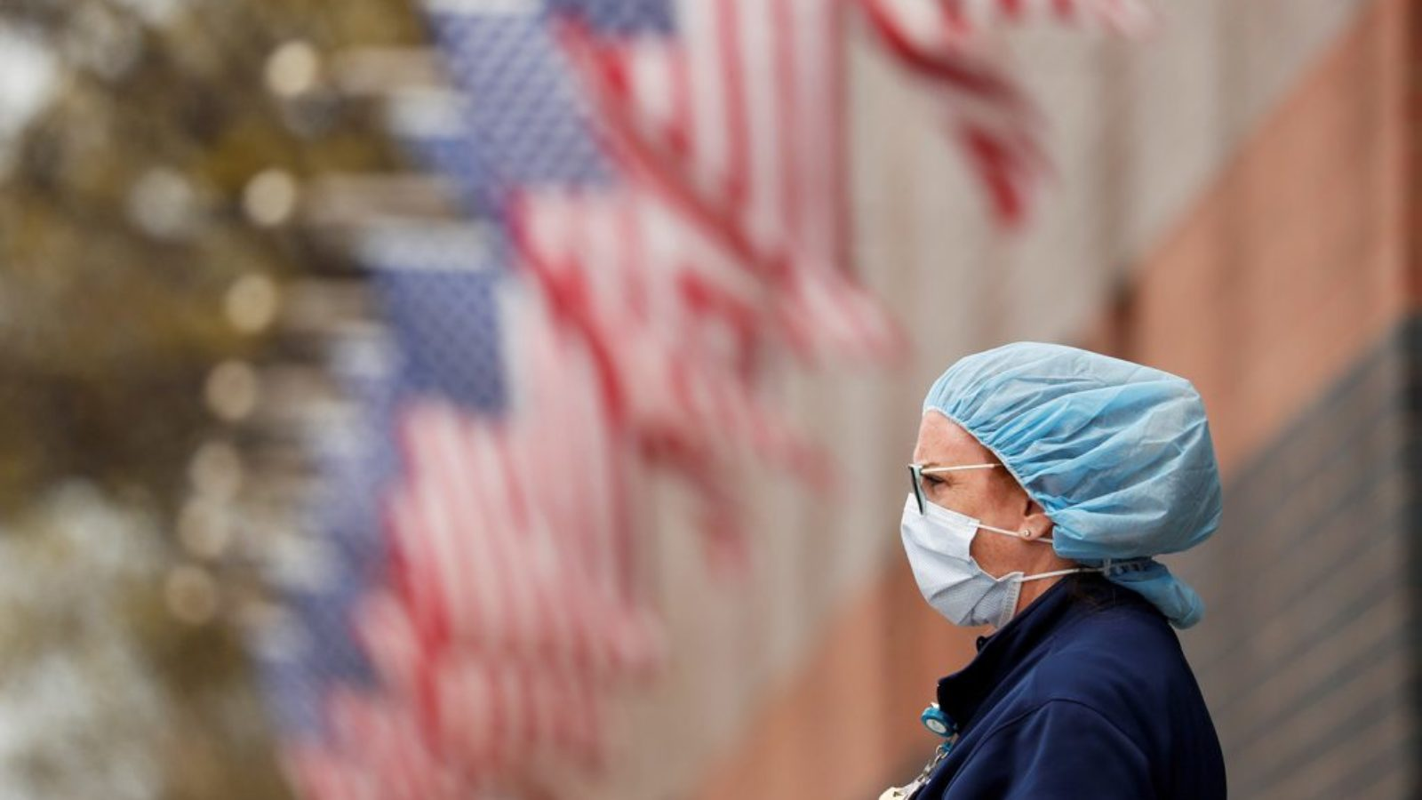 A nurse wearing personal protective equipment in front of a row of American flags