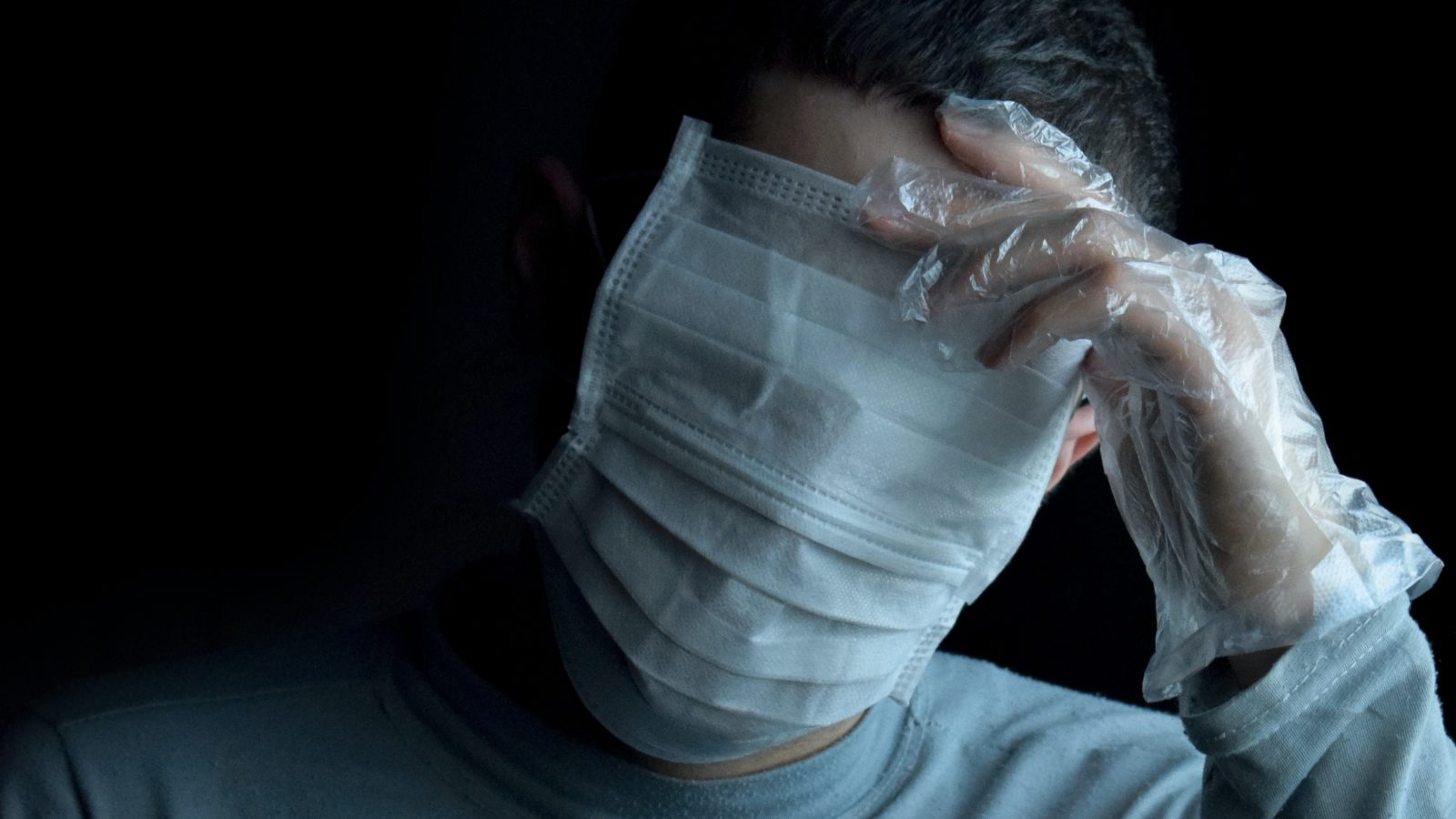 A man wears two face masks that cover his face and eyes in front of a black background.