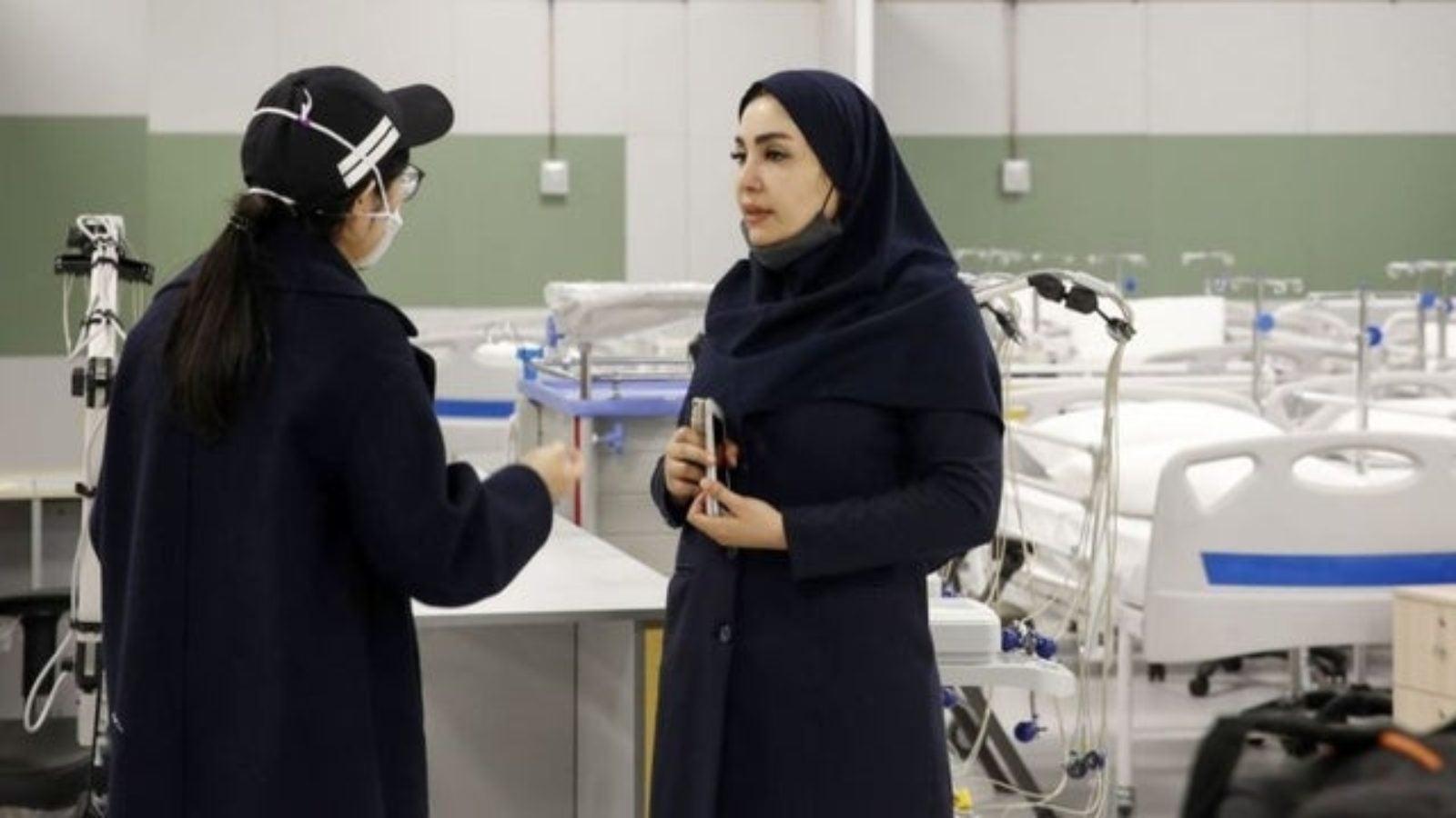 Women in black clothing speak in front of empty hospital beds