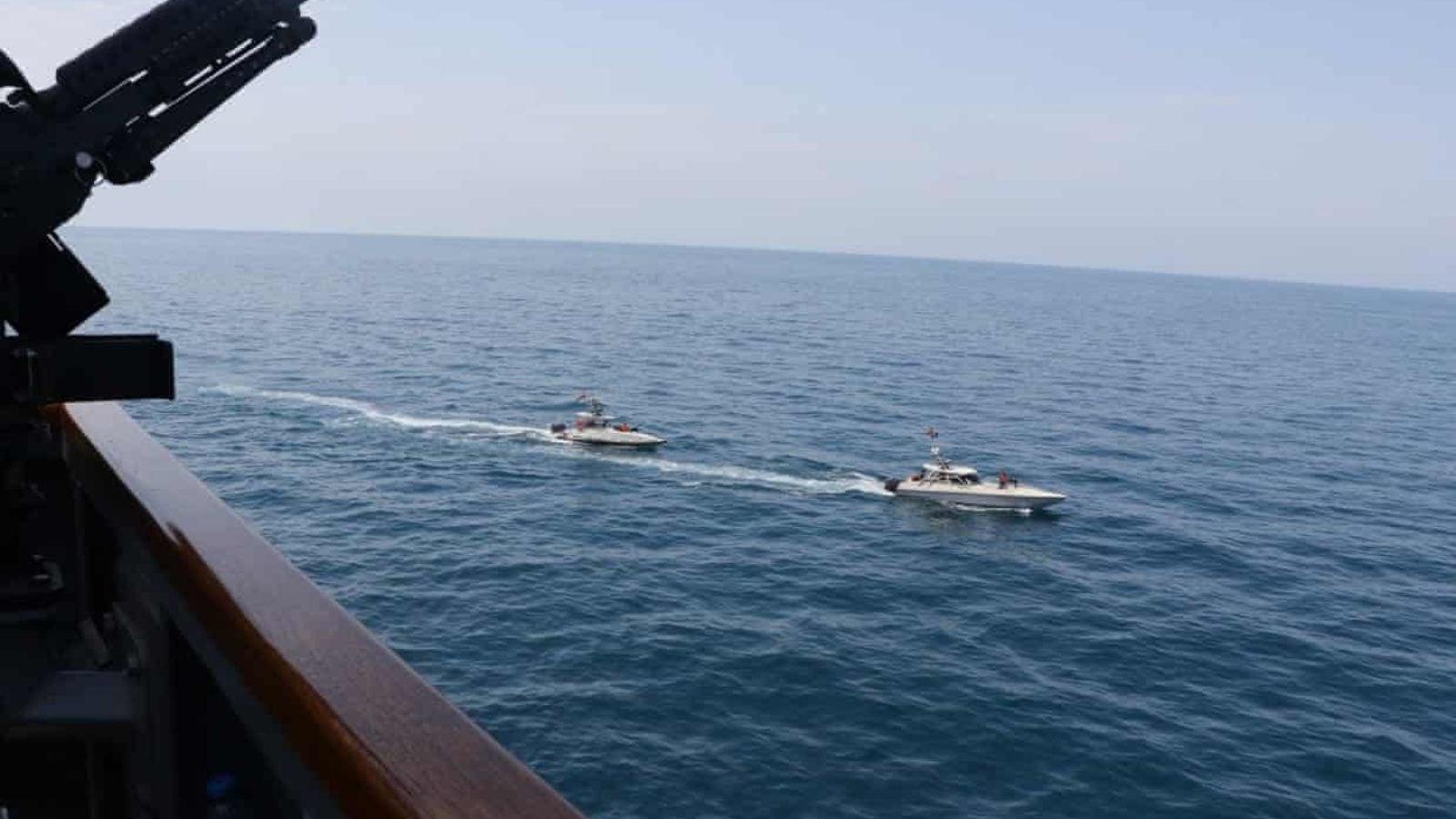 Two small Iranian vessels sail close to a U.S. Navy ship