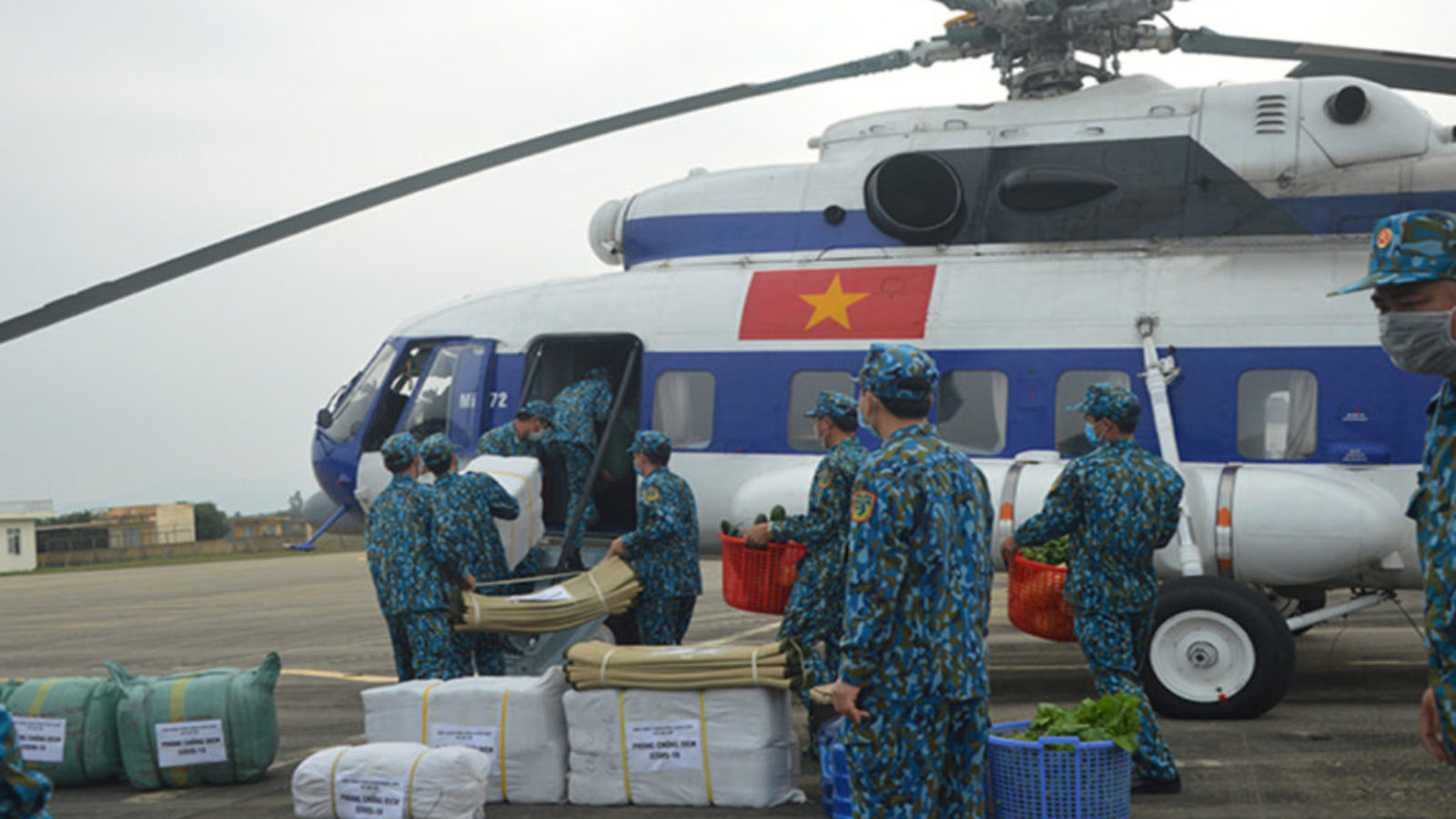 Soldiers in blue camouflage load supplies onto a helicopter with the Vietnamese flag