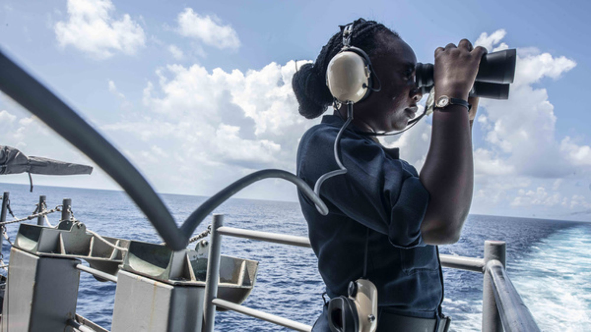 A seaman uses binoculars while standing aboard the U.S. Navy aircraft carrier USS Ronald Reagan.
