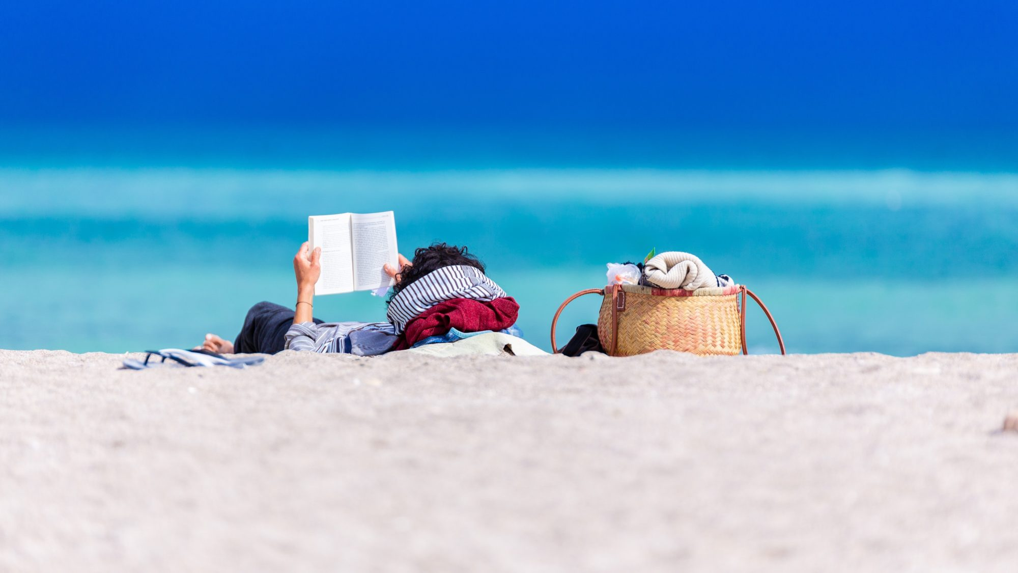 A person reads a book while reclining on a beach