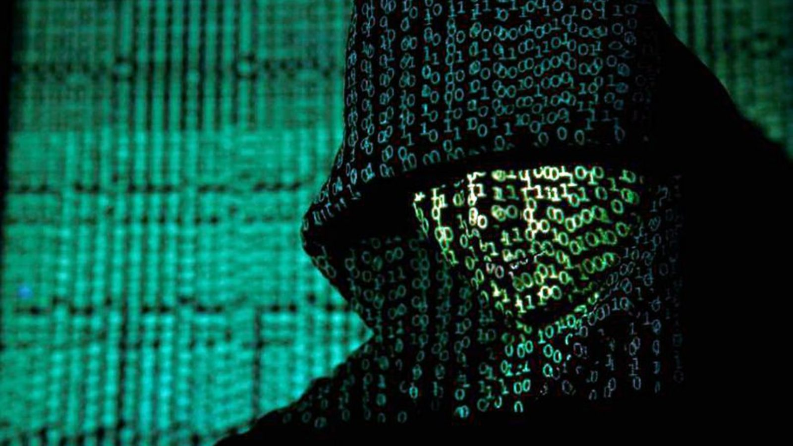Green lines of code are projected on the face of a man earing a dark hoodie