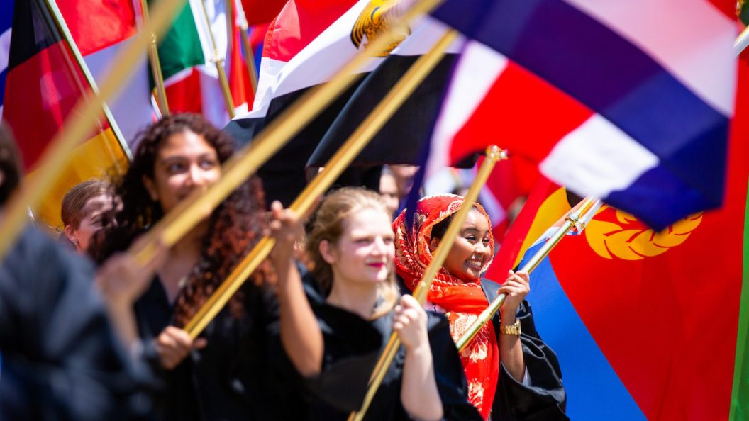 SFS students hold their countries' flags at Convocation