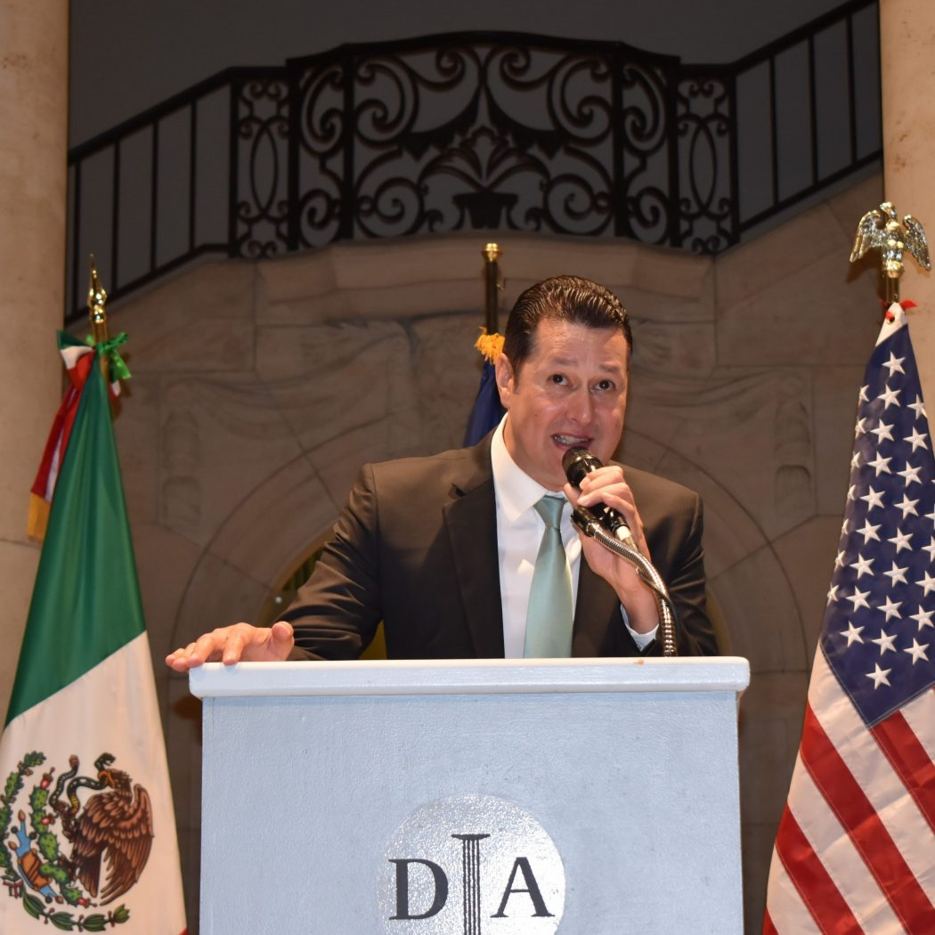 Christian Clay speaks at a podium in front of the US and Mexican flags