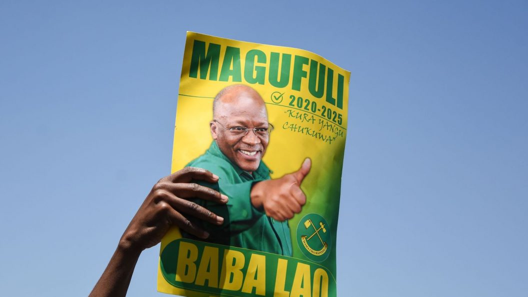 A hand holds up a green and yellow sign that shows John Magufuli