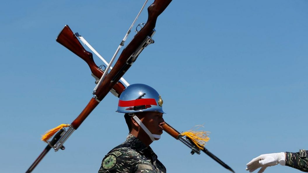 A Taiwanese soldier stands in front of two rifles during a military drill.