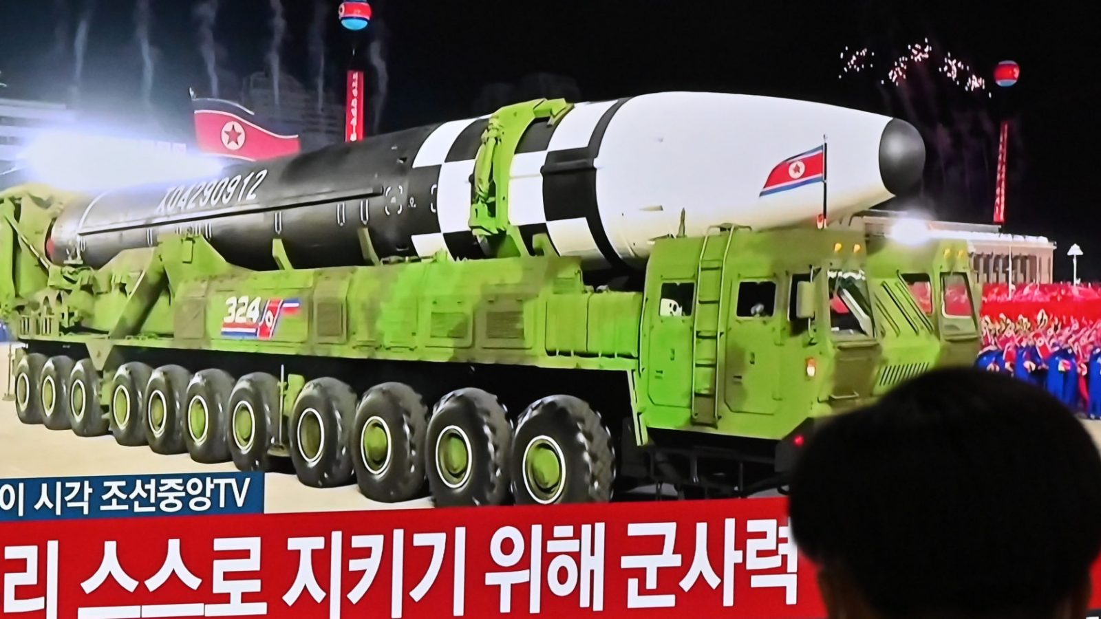 A man watches a television screen showing Korean characters and a North Korean missile on a green military truck.