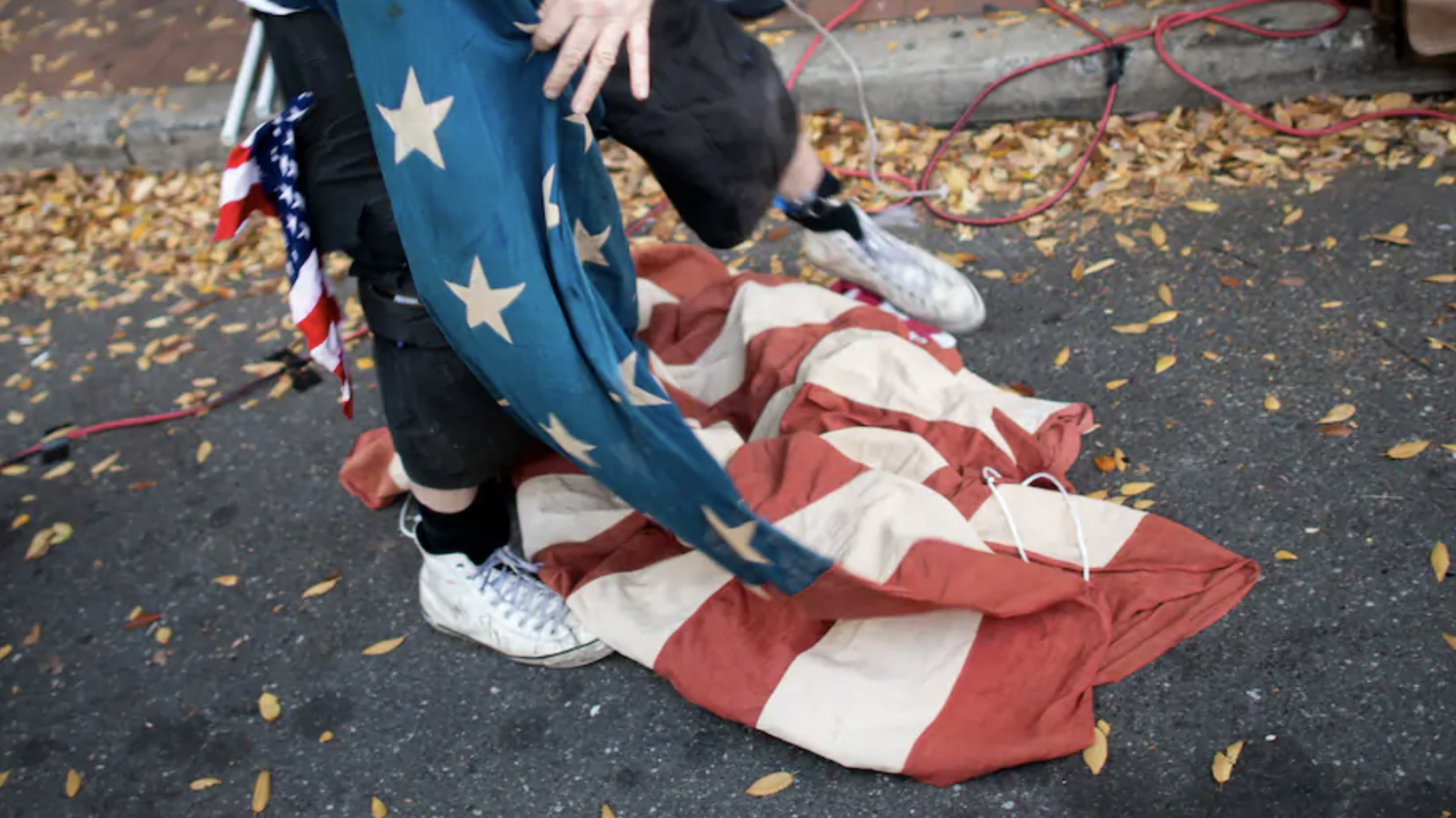 A hand unfurls an American flag from the ground.