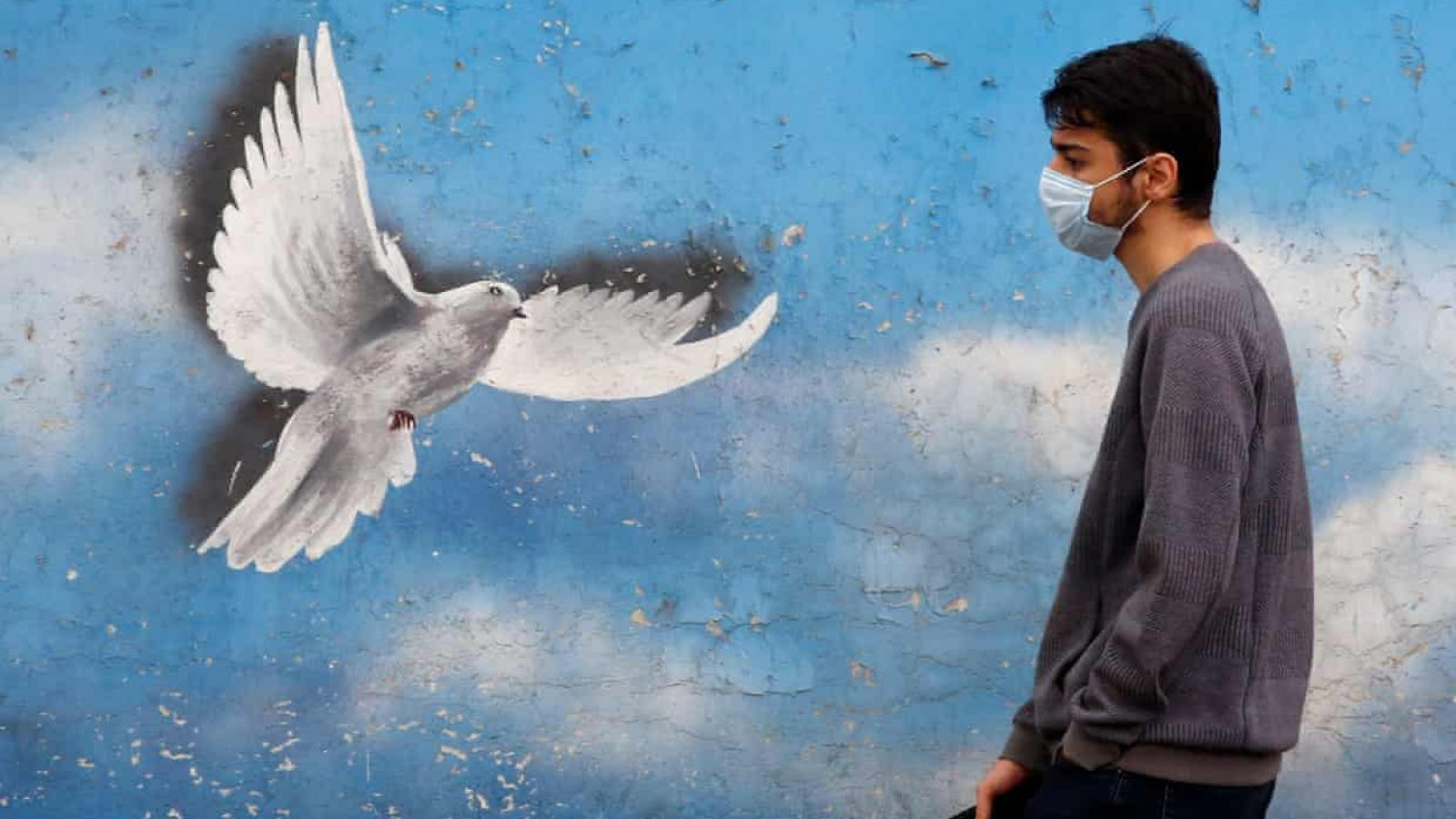 A man in a medical mask walks by a mural of a flying dove against a sky background