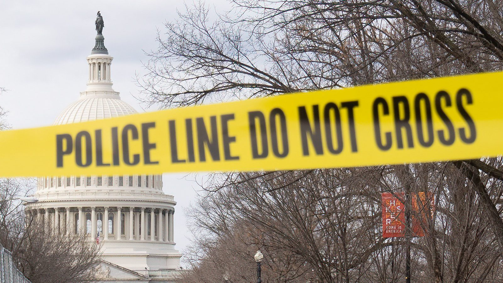The Capitol Building is framed by a yellow police tape that reads