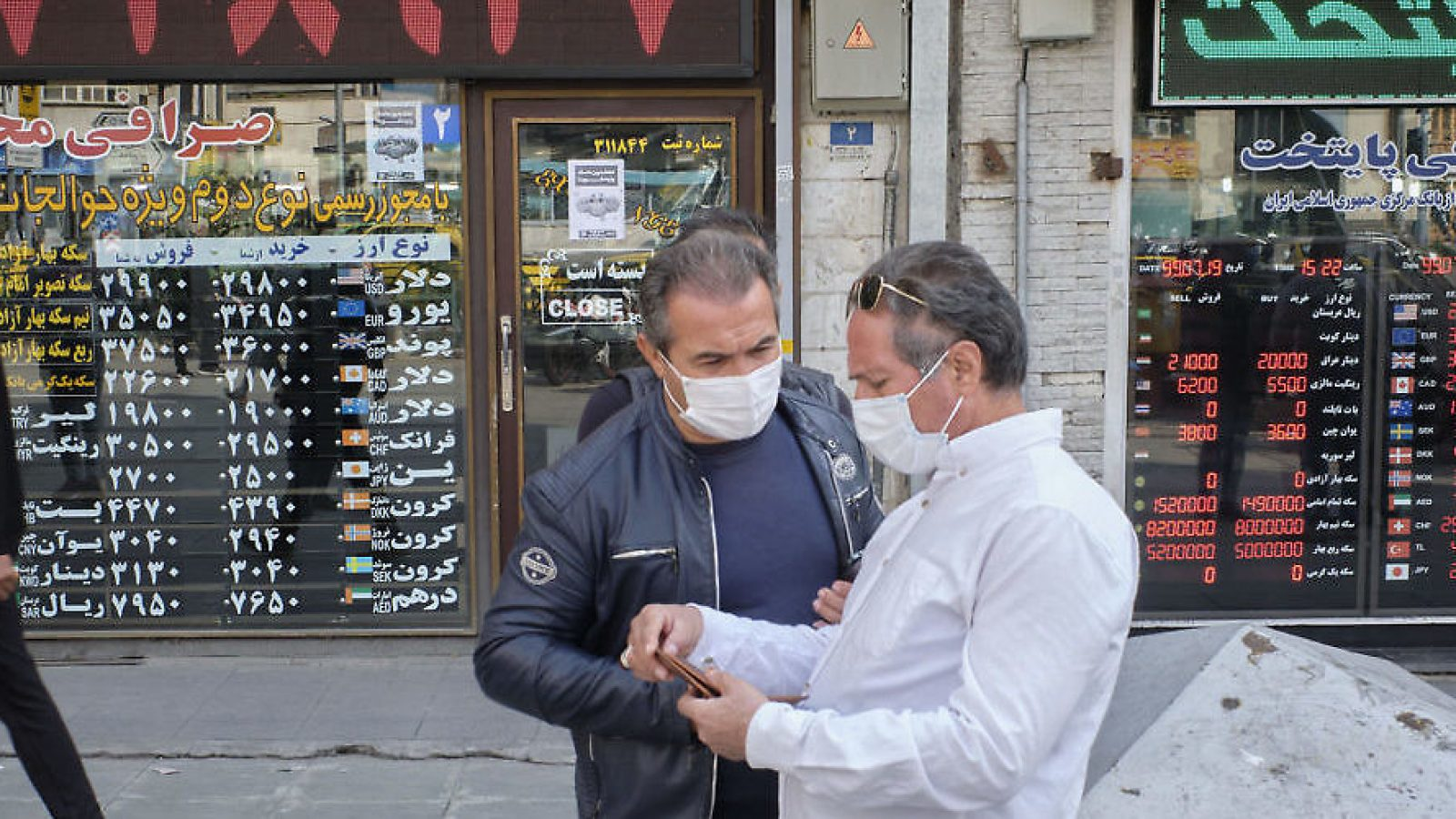 Two men in masks stand together in front of shops in Tehran.