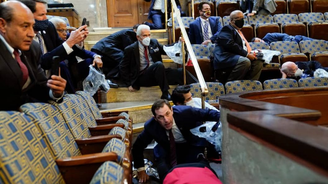 People duck beneath seats in the House gallery
