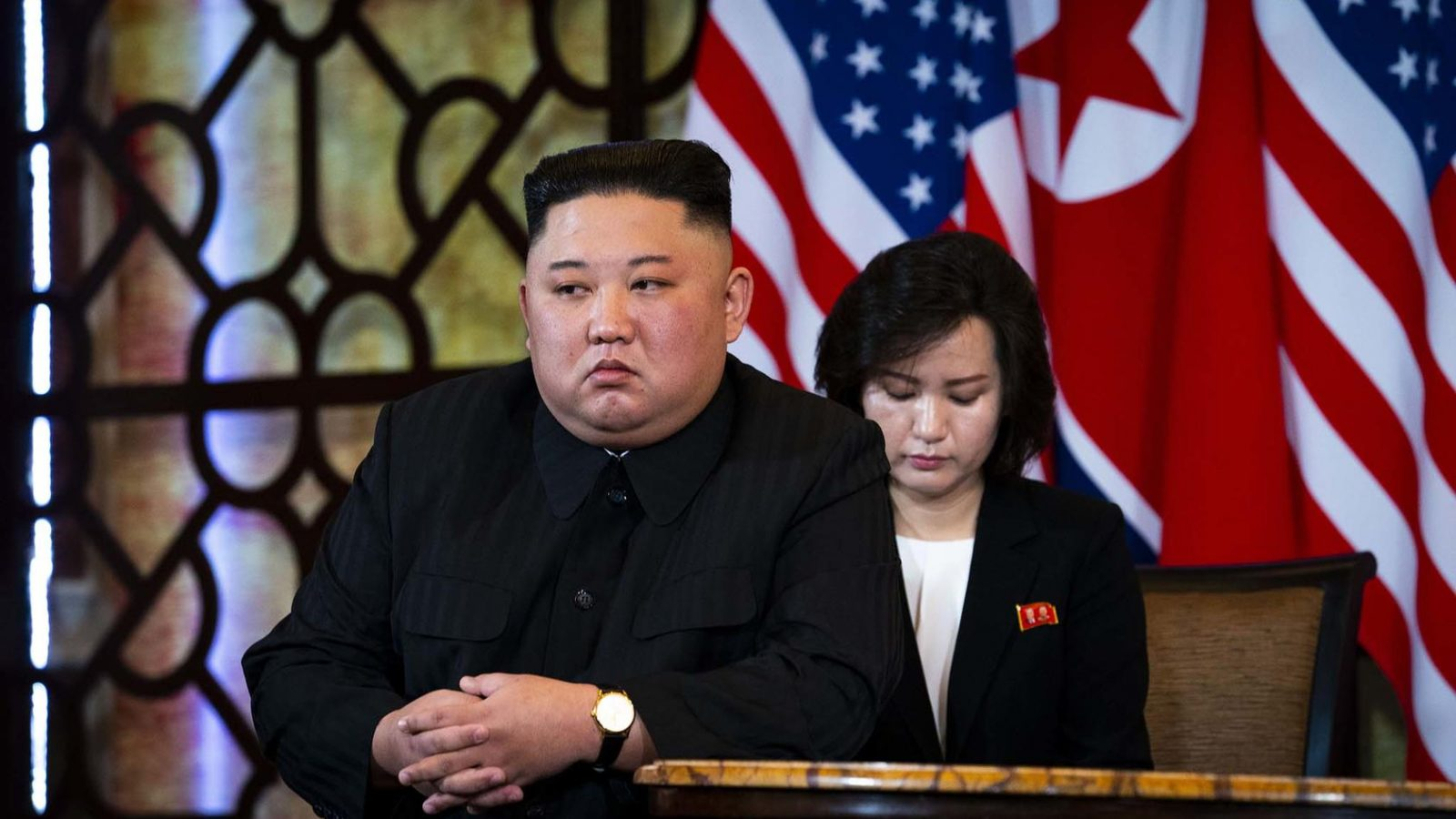 Kim Jon-un sits at the front of a table with a woman behind him and North Korean and American flags in the background.