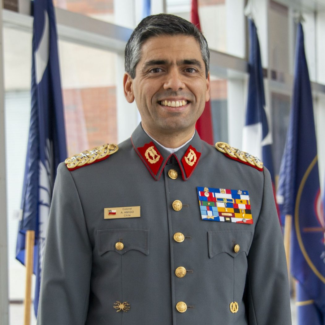 Headshot of Col. Alejandro Amigo in a glass hallway in front of various flags, dressed in a grey Chilean army uniform