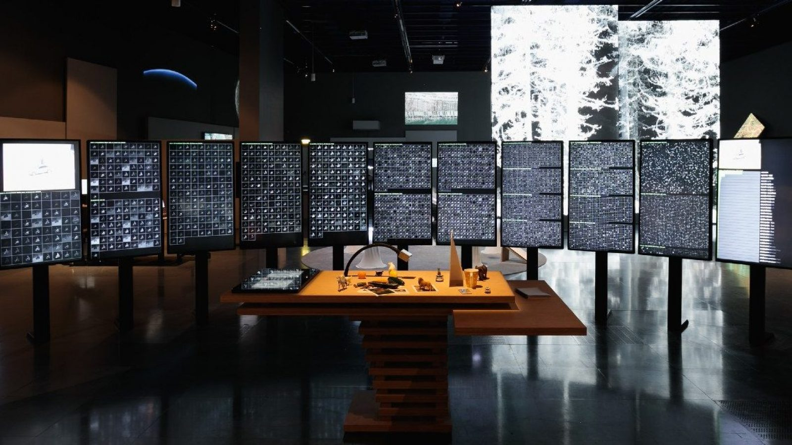A dark room with many screens that show what appear to be small photo negatives.