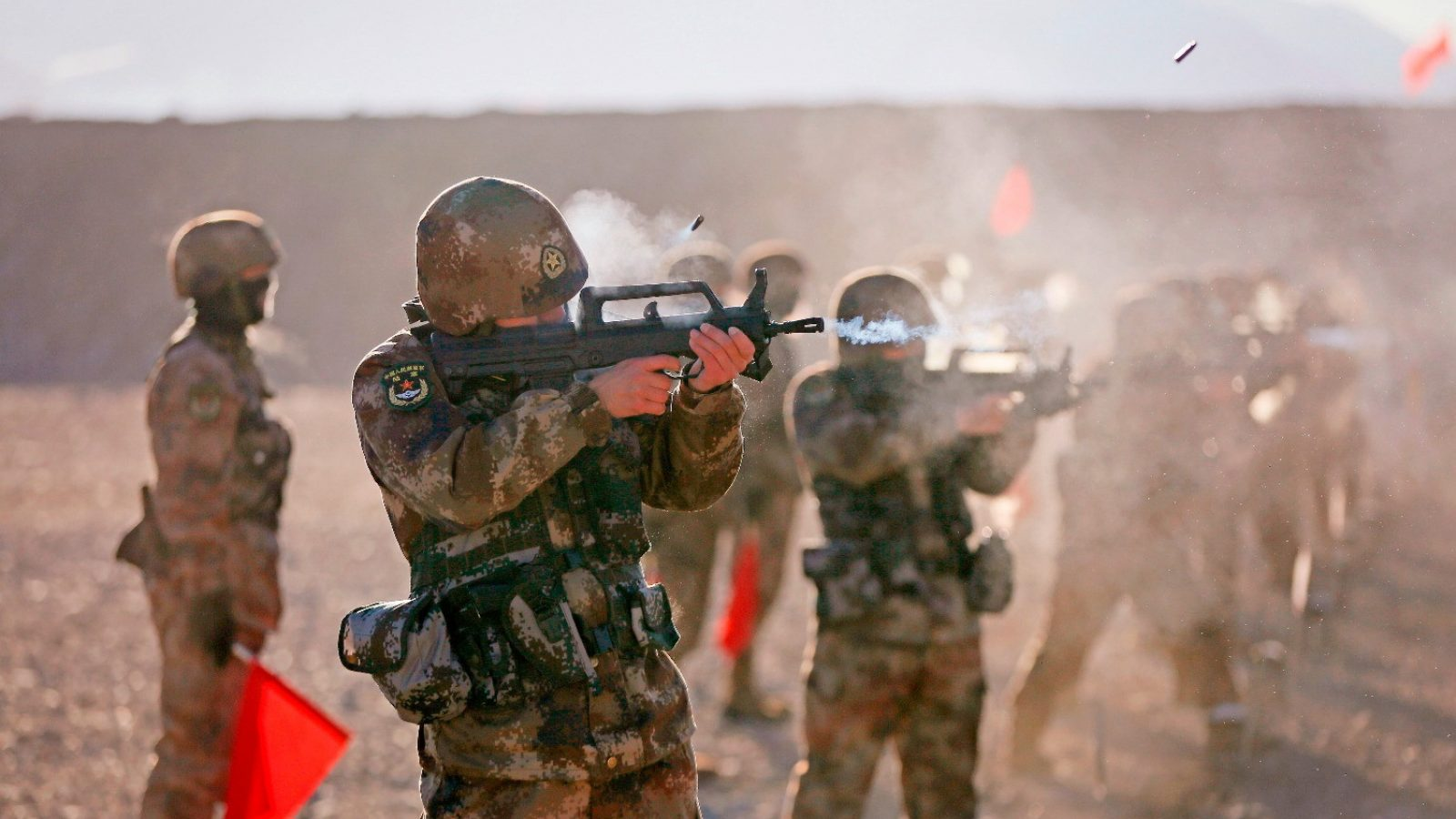 Members of the PLA fire rifles at a military training ground.