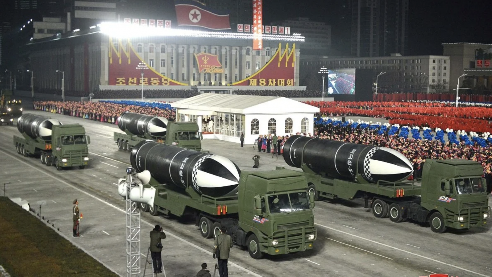 Four green military trucks carrying large submarine launched missiles proceed in a nighttime parade in North Korea.