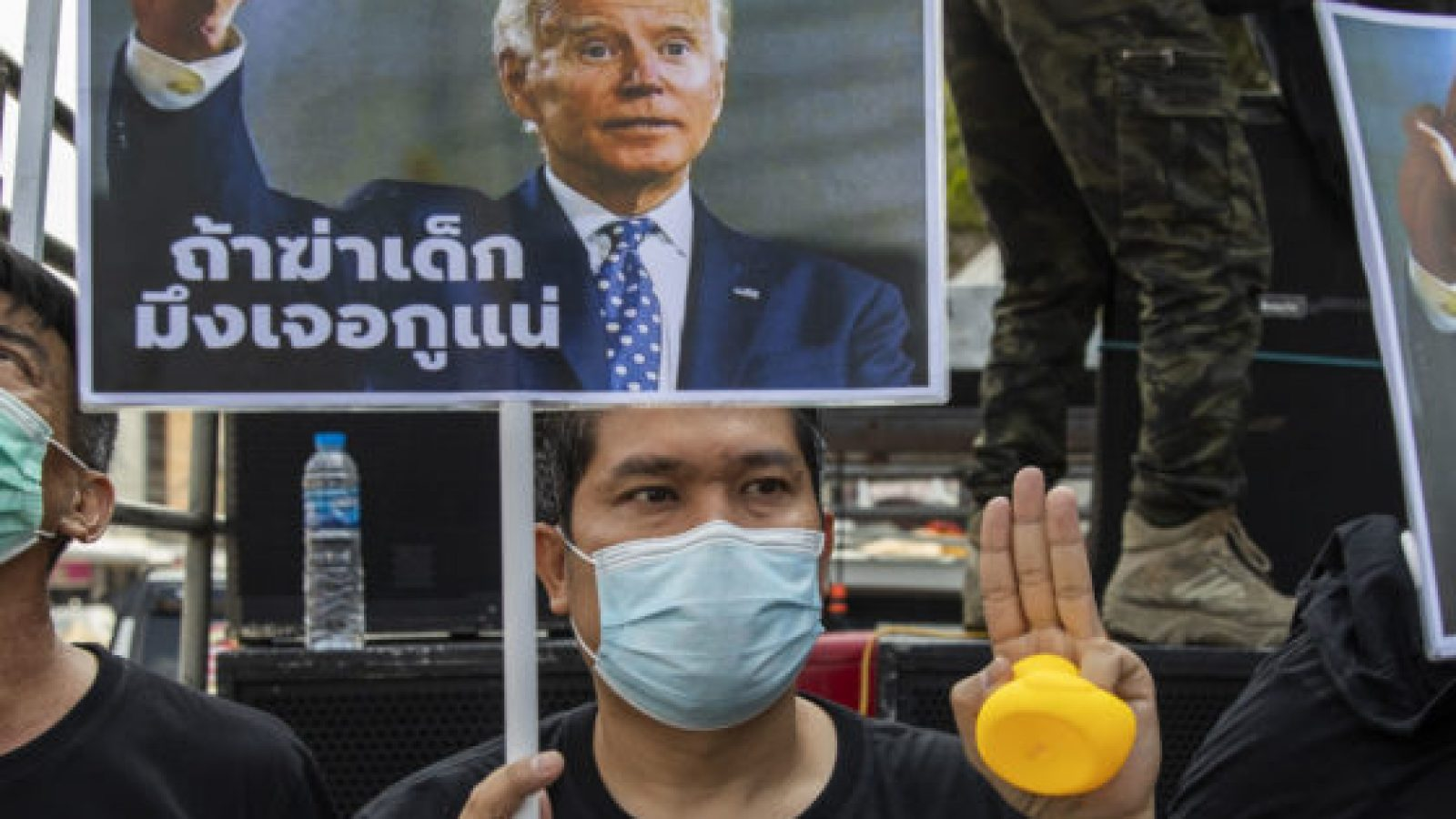 Protestors in medical masks hold posters of Joe Biden with Thai text