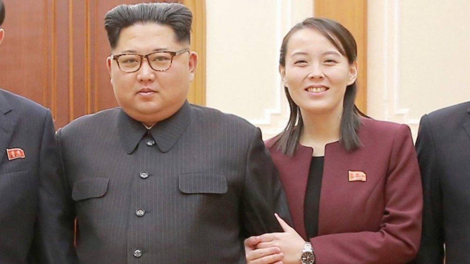 Kim Yo Jong holds Kim Jong Un's arm as they pose for a photo