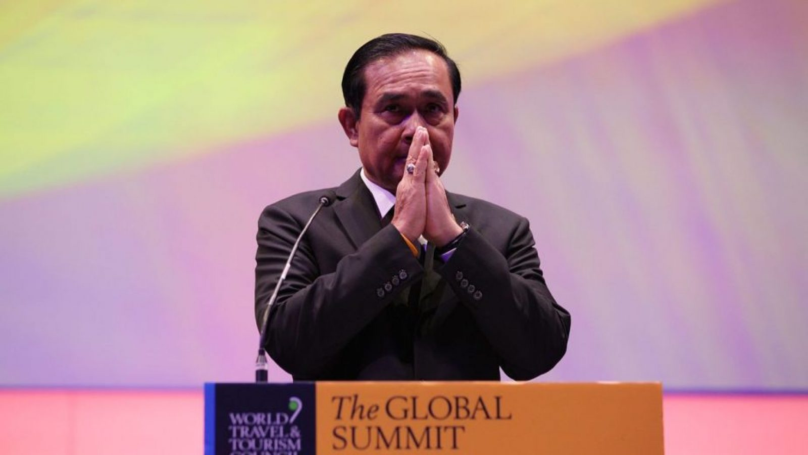 The Thai Prime Minister clasps his hands together behind a podium at The Global Summit in Bangkok