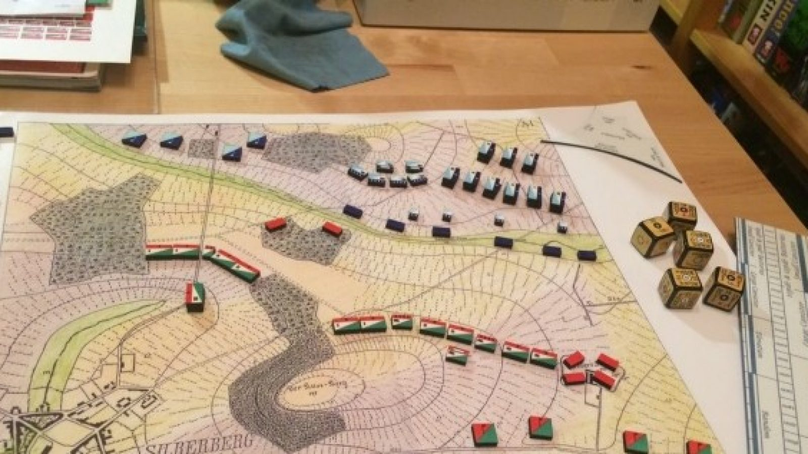 A photo of a wargaming board with pieces on a terrain map
