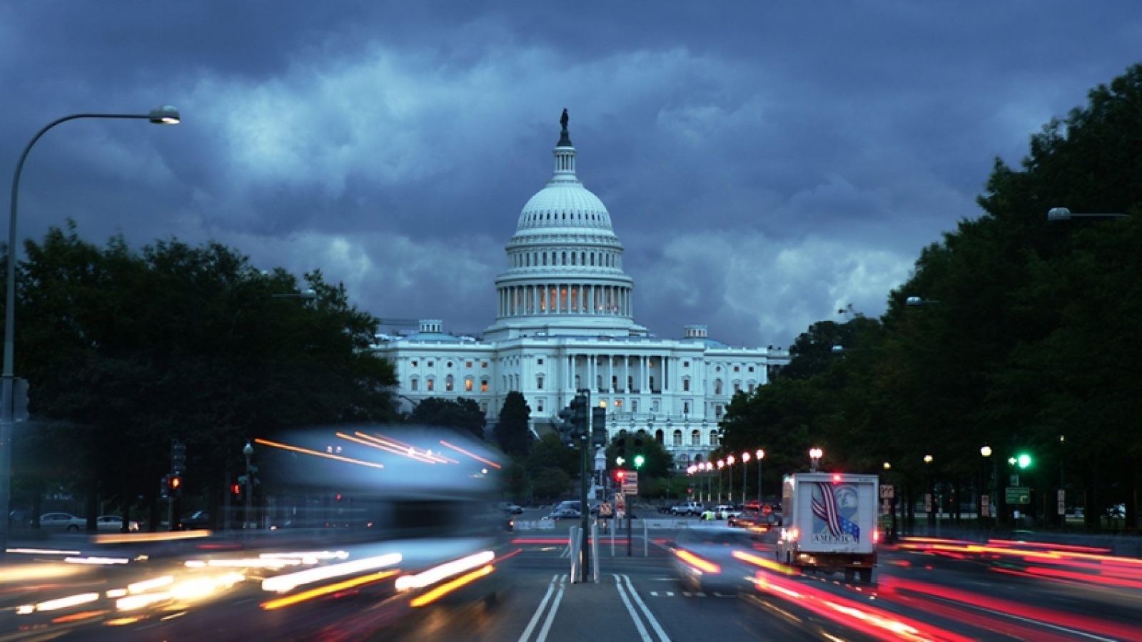 Cars drive in front of the U.S. Capitol Building on a dark stormy evening