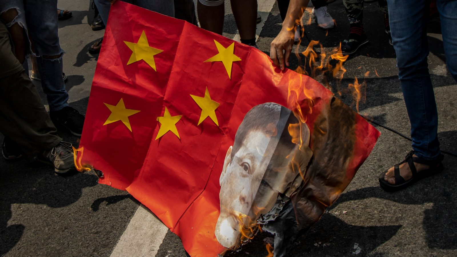 A mock Chinese flag with Rodrigo Duterte's face is burned by protestors on the street