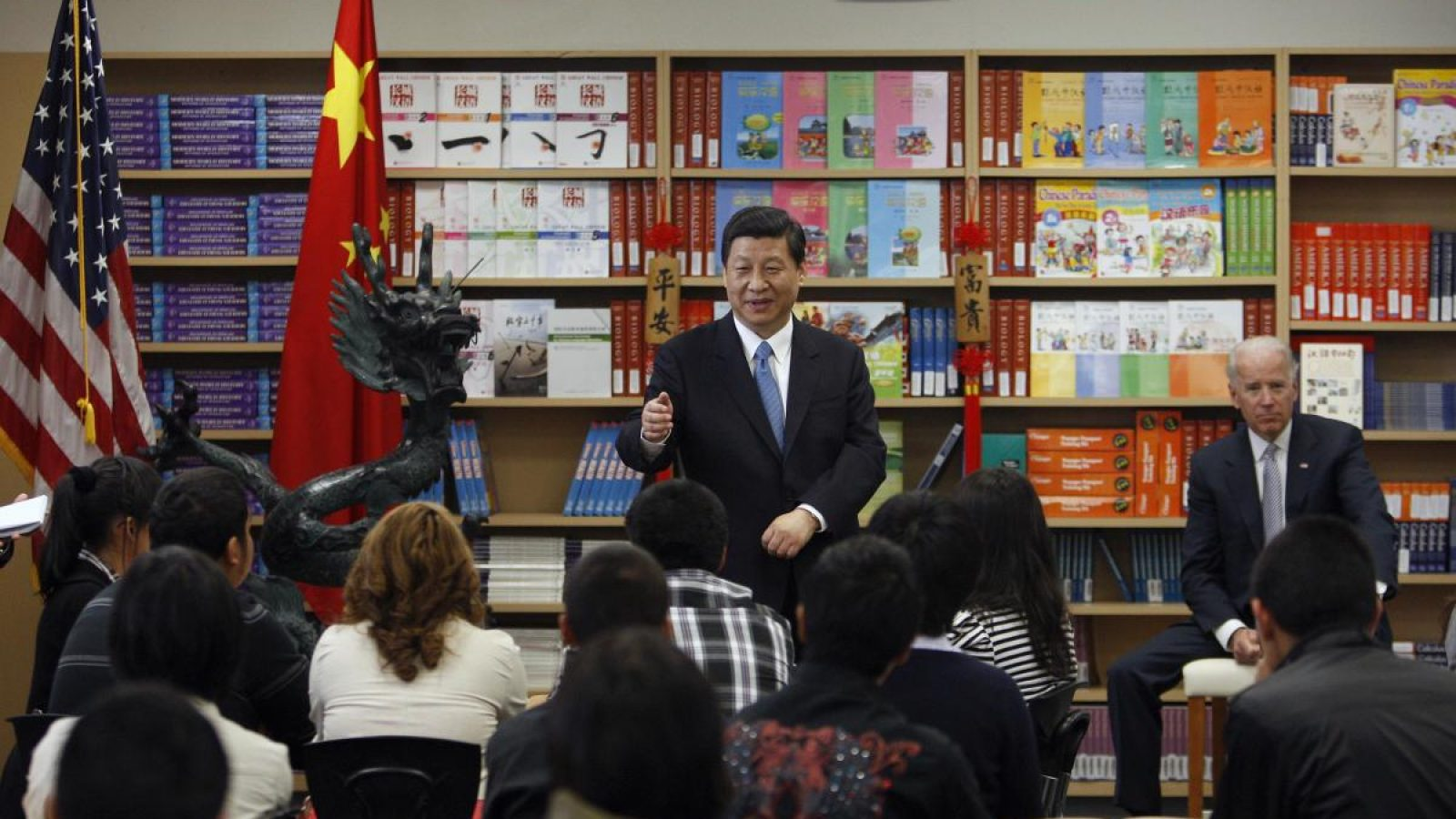Xi Jinping points at a classroom of students while a sitting Joe Biden looks on in the background