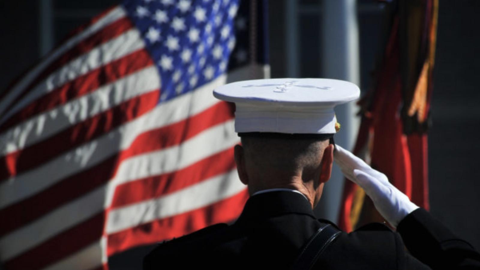 A man in a military uniform salutes U.S. flags