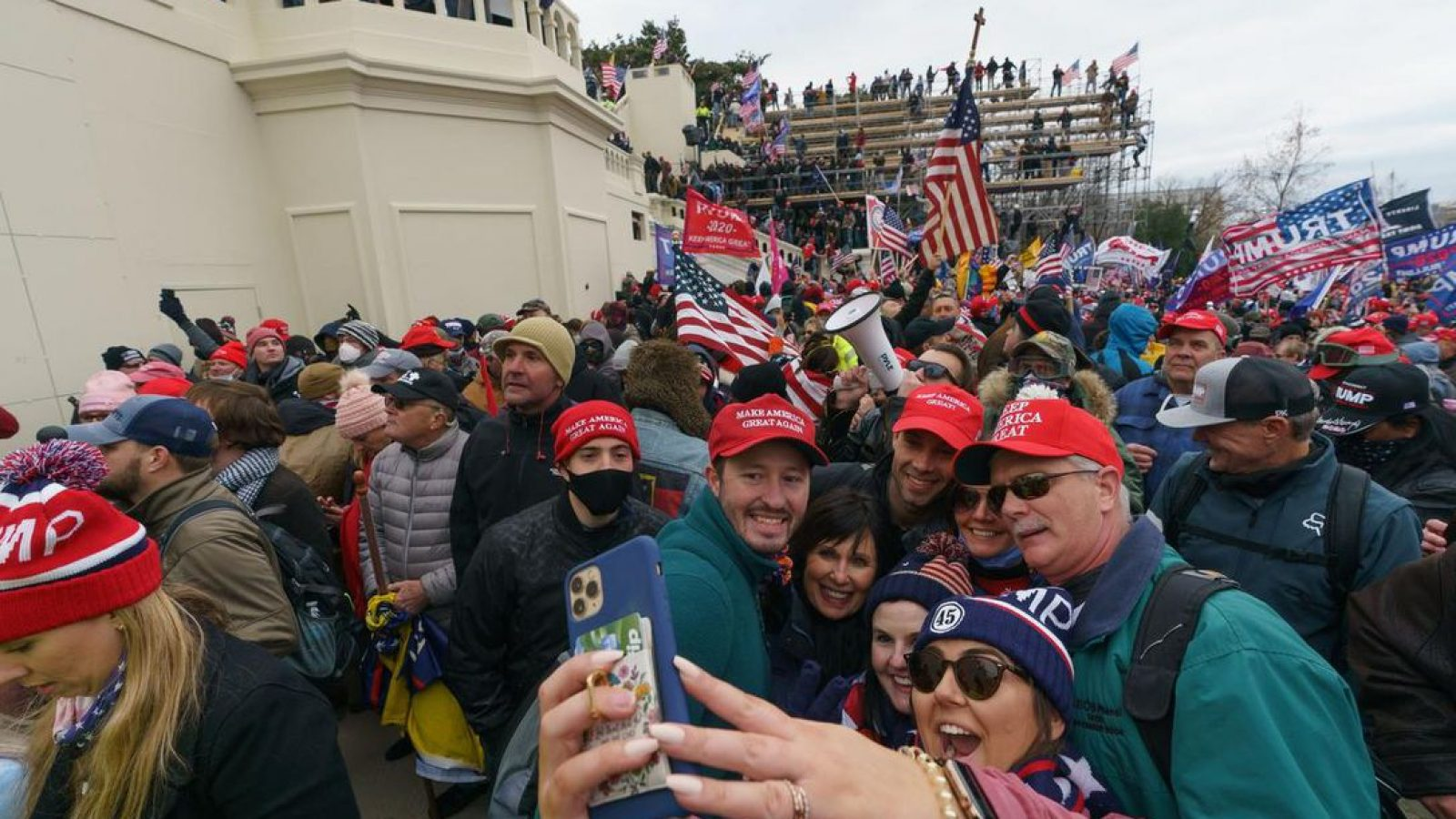 A large crowd of rioters, many wearing red MAGA hats, crowd and take selfies in front of the Capitol steps.