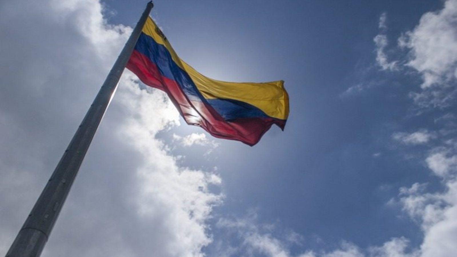 The Venezuelan flag flies against a sunny blue sky with clouds